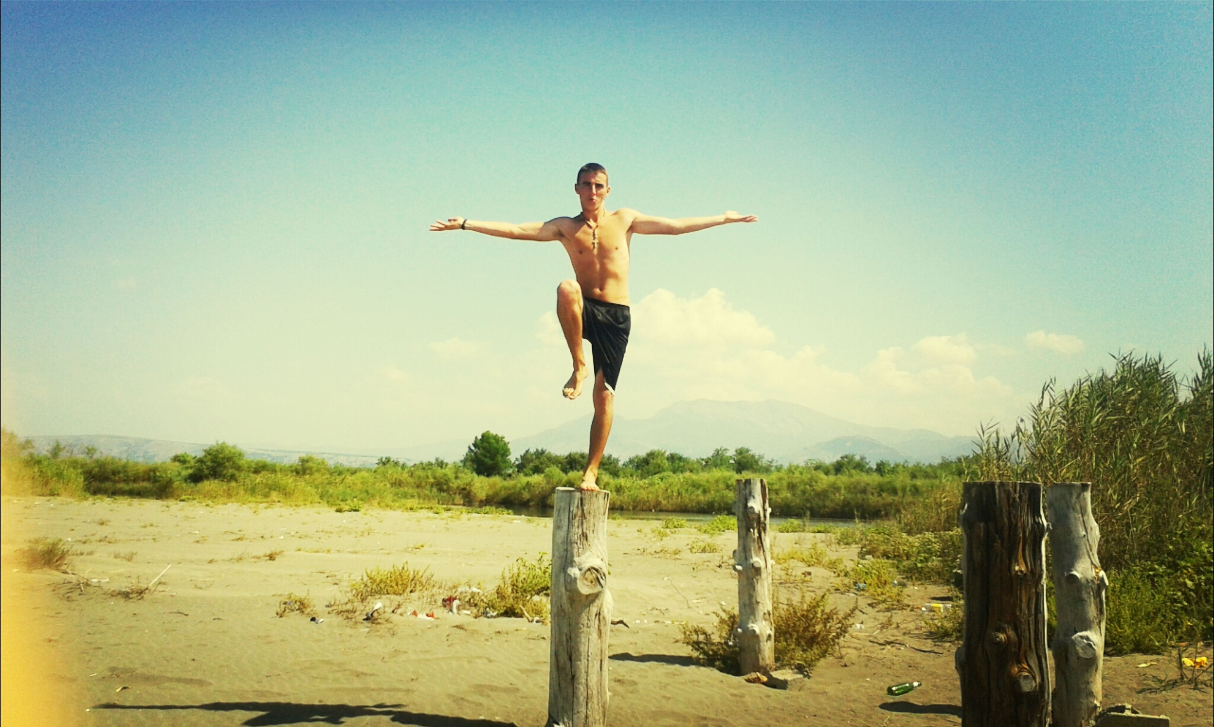 full length, human representation, sky, art and craft, sculpture, clear sky, art, creativity, statue, sunlight, landscape, blue, arms outstretched, one person, tree, tranquility, jumping, day, nature