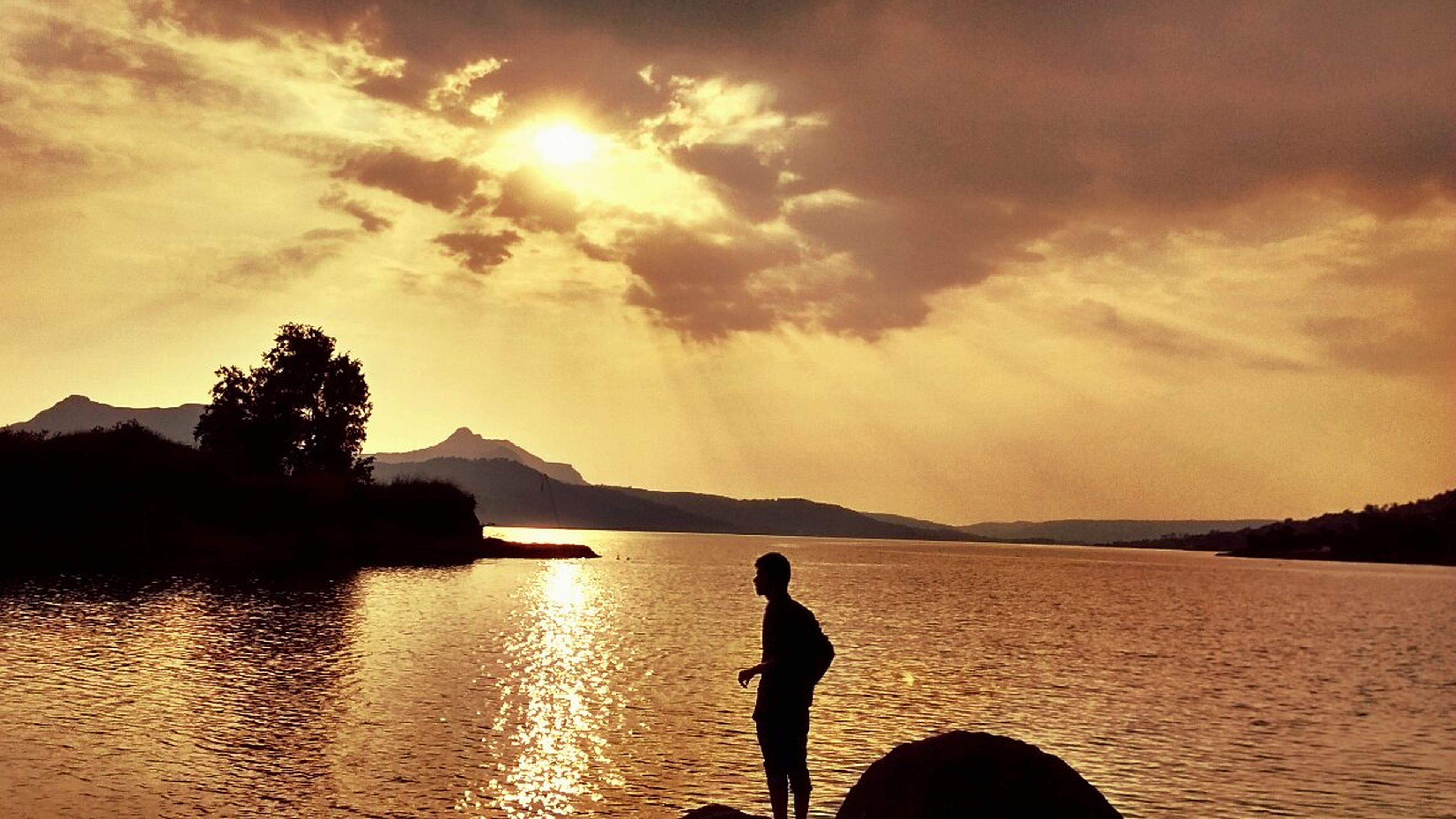 water, silhouette, sky, tranquil scene, scenics, sunset, tranquility, beauty in nature, nature, cloud - sky, sea, leisure activity, idyllic, lifestyles, standing, sun, mountain, reflection