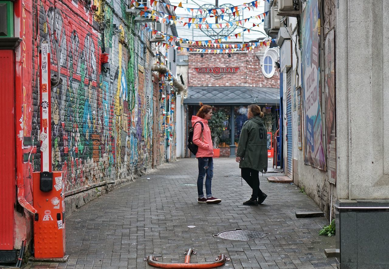 graffiti, real people, full length, walking, two people, architecture, rear view, men, built structure, day, women, building exterior, lifestyles, standing, multi colored, outdoors, adult, people, adults only