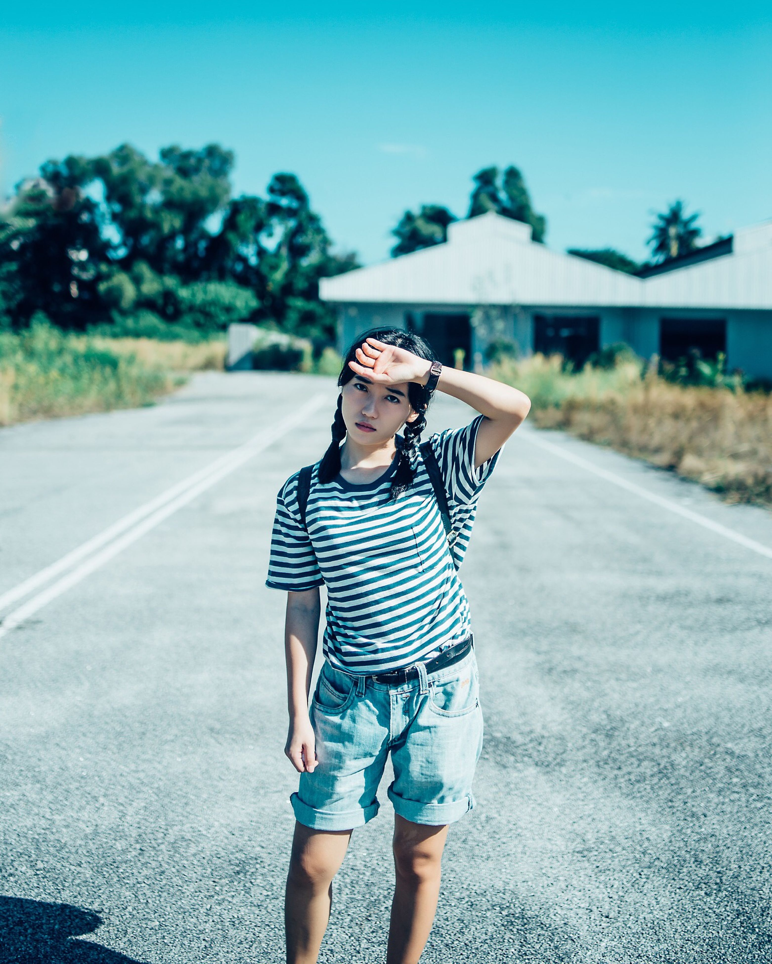 lifestyles, road, leisure activity, casual clothing, young adult, standing, sunlight, street, rear view, young women, transportation, person, day, full length, clear sky, outdoors, front view, sky