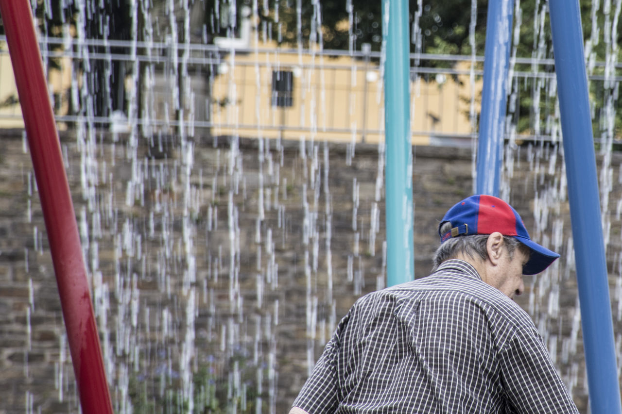 Building Exterior Casual Clothing City Life Day Focus On Foreground Fountain Fun Hat Men People And Places Red And Blue Red And Blue Colors Weekend Activities