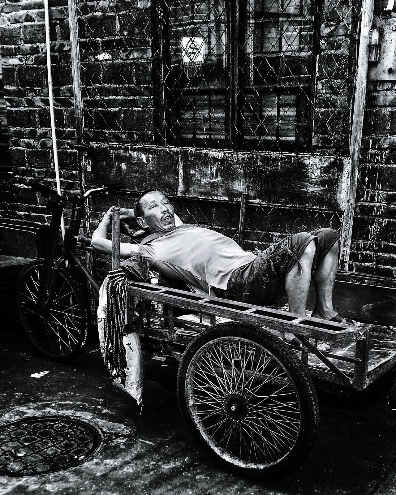 在南泰路批发市场附近,三轮车夫在休息。如果有东西要运的话,雇主会叫醒他们,然后讨价还价。如果要搬货物上楼或者搬上大货车的话需要加钱。Street Snap 沉睡的中国人 散工 Outdoors Person Casual Clothing Bicycle Sleeping Chinese