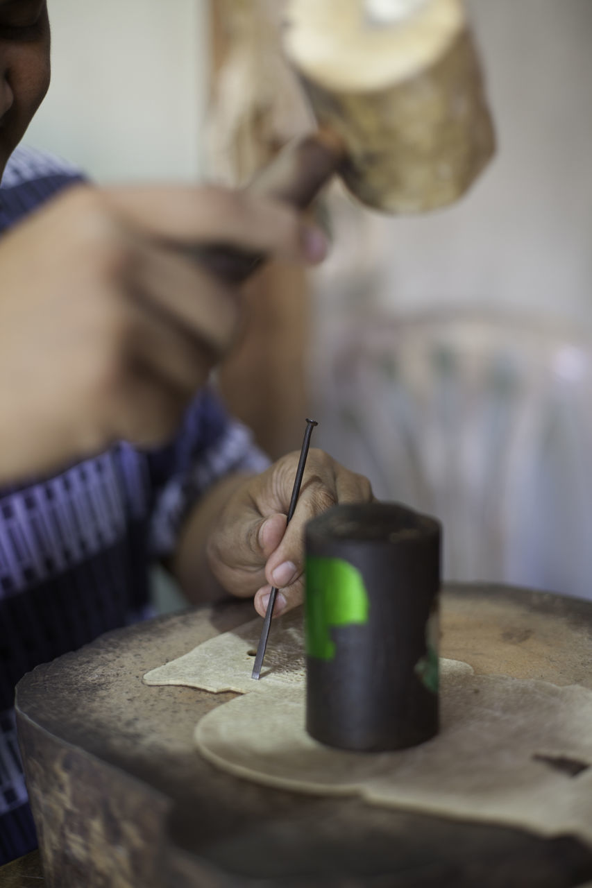 Cropped Image Of Person Using Hammer And Nail On Leather