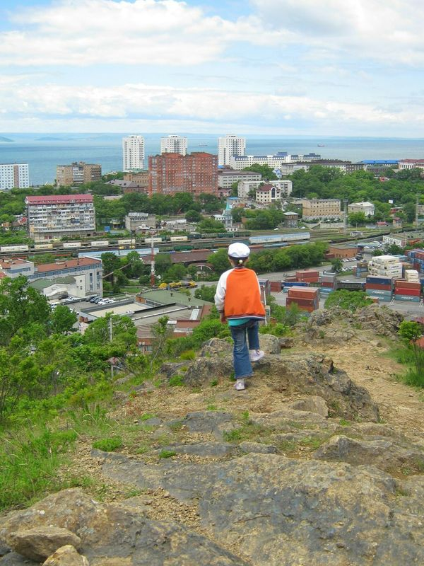 Girl standing on the top of the mountain over the city One Person Girl City Cityscape Outdoors Sky Cloud - Sky Built Structure Town Day Building Exterior Architecture Residential Building Rear View Standing Looking At View On The Top Of The Mountain On The Top Sea Horizon Over Water Summer