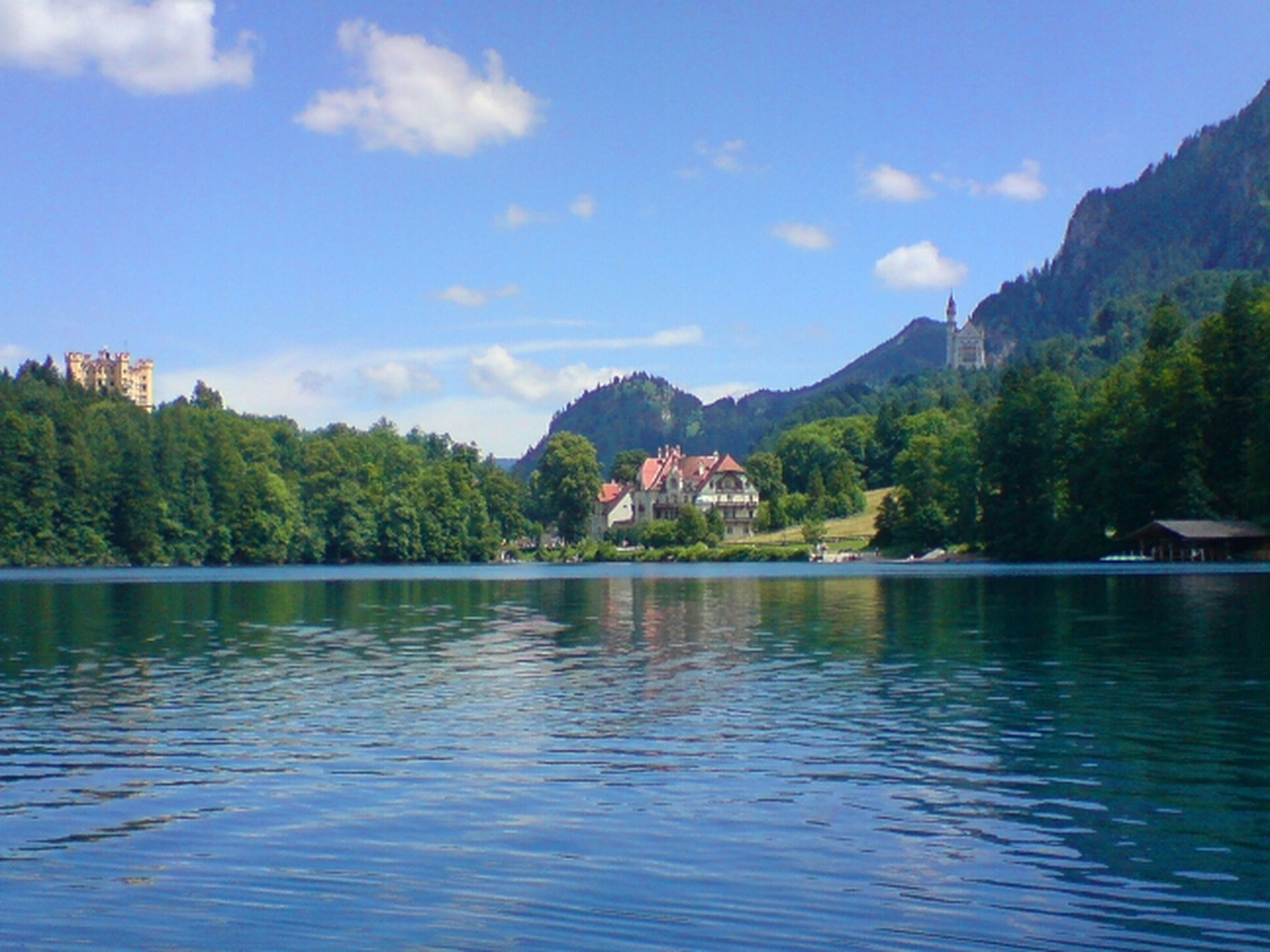 mountain, water, tree, sky, waterfront, lake, tranquil scene, scenics, tranquility, mountain range, beauty in nature, cloud, cloud - sky, nature, building exterior, reflection, river, built structure, blue, idyllic