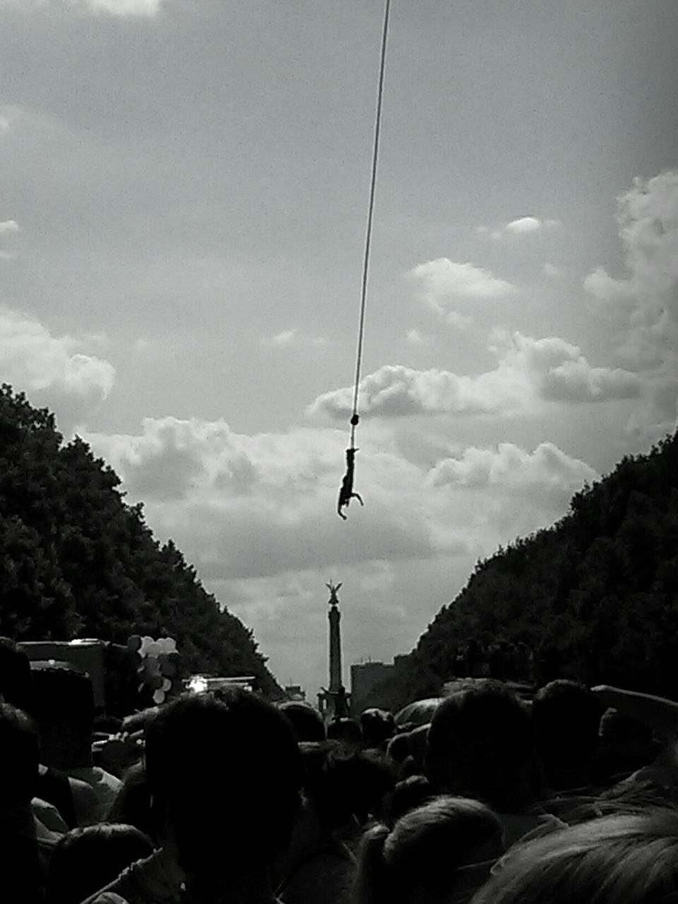 People Watching Bungee Jumping Against Sky