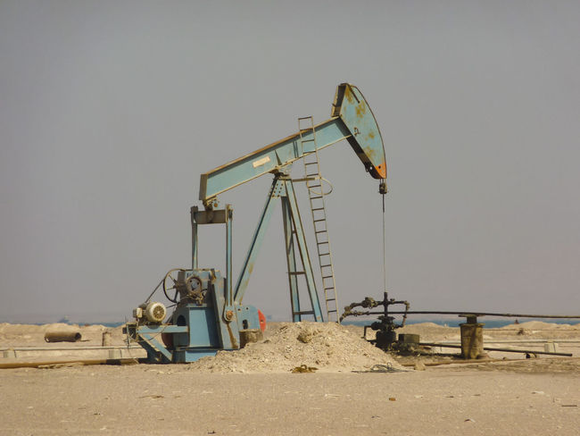 Beach Beam Pump Built Structure Clear Sky Copy Space Day Desert LPG Nodding Donkey Oil Oil And Gas Oil And Gas Industry Oilfield Outdoors No People Old Sand Sea Shore Sky Stone Sunlight Tank Water Pump