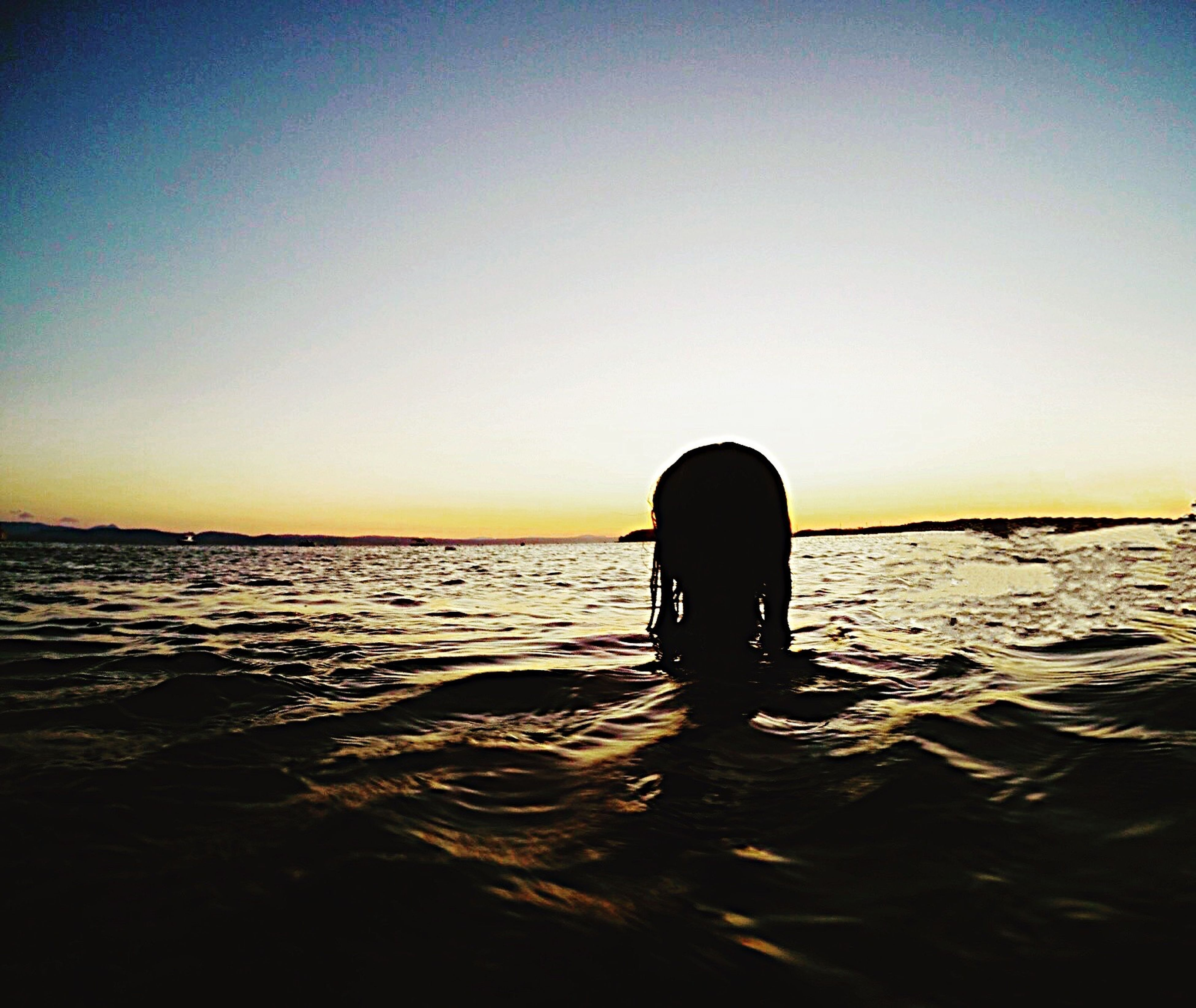 silhouette, sea, standing, copy space, clear sky, relaxation, horizon over water, water, tranquility, tranquil scene, escapism, scenics, alone, person, waterfront, rippled, blue, nature, solitude, beauty in nature, remote, getting away from it all, day, ocean, weekend activities, vacations