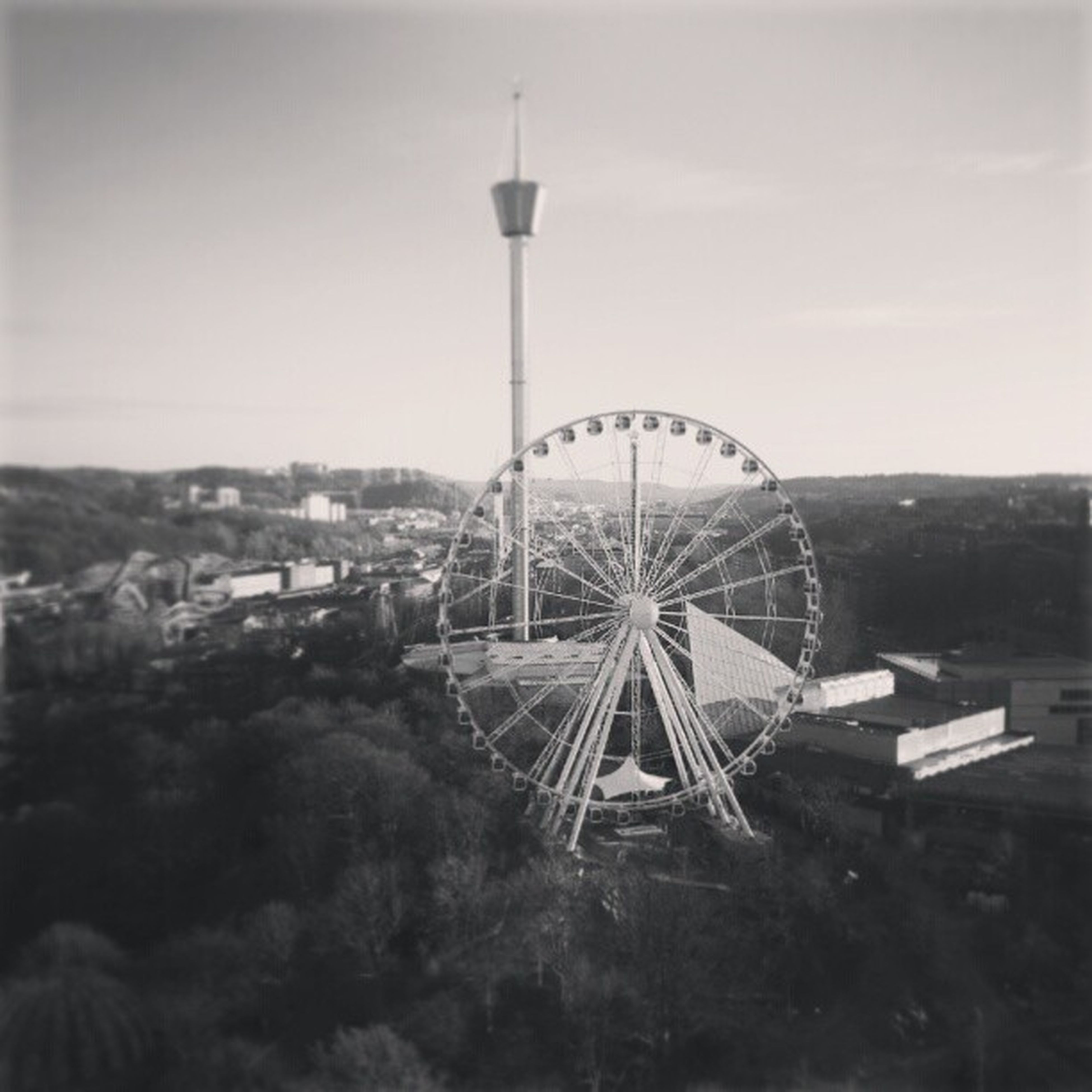 ferris wheel, amusement park, sky, amusement park ride, built structure, architecture, building exterior, arts culture and entertainment, outdoors, city, technology, tall - high, communications tower, no people, low angle view, day, tower, clear sky, cloud - sky, travel destinations