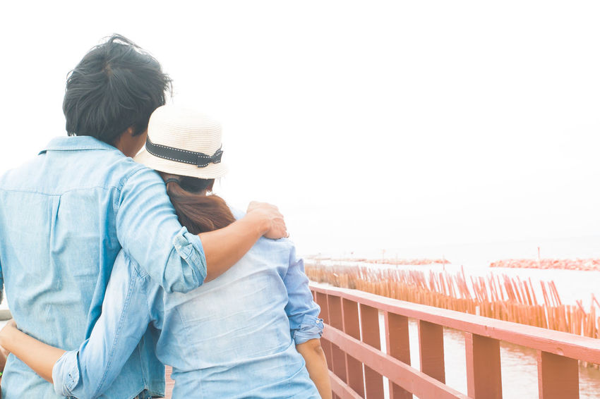 Happy asian couple looking foreword standing on bridge ASIA Asian  Beautiful Copy Space Hug Man Natural Nature Adult Casual Clothing Day Leisure Activity Lifestyles Love Nature Outdoors People Real People Rear View Seaside Standing Togetherness Two People Women