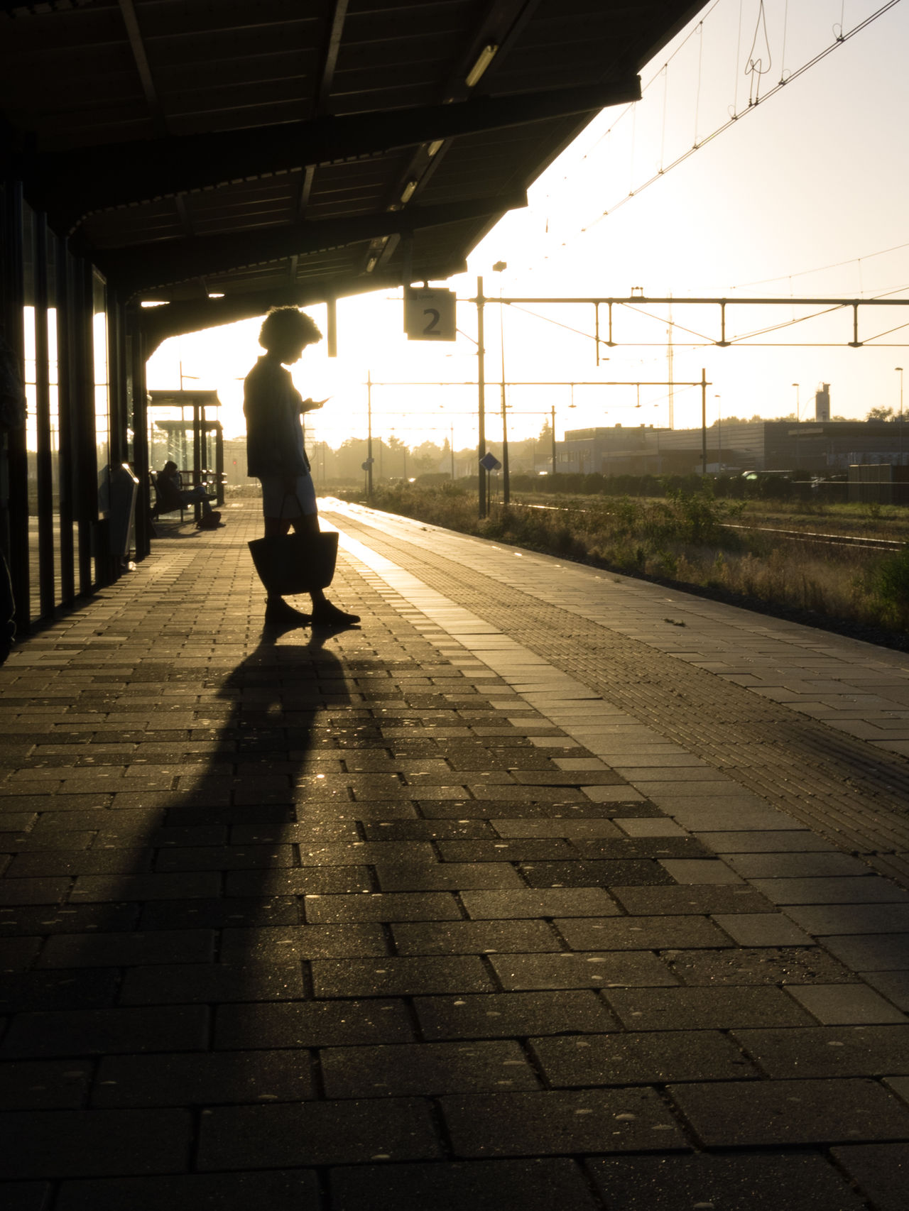 Adult Adults Only Commute Copy Space Full Length Morning One Person People Person Perspective Platform Real People Silhouette Station Sunrise The City Light Unrecognizable Person Waiting Woman