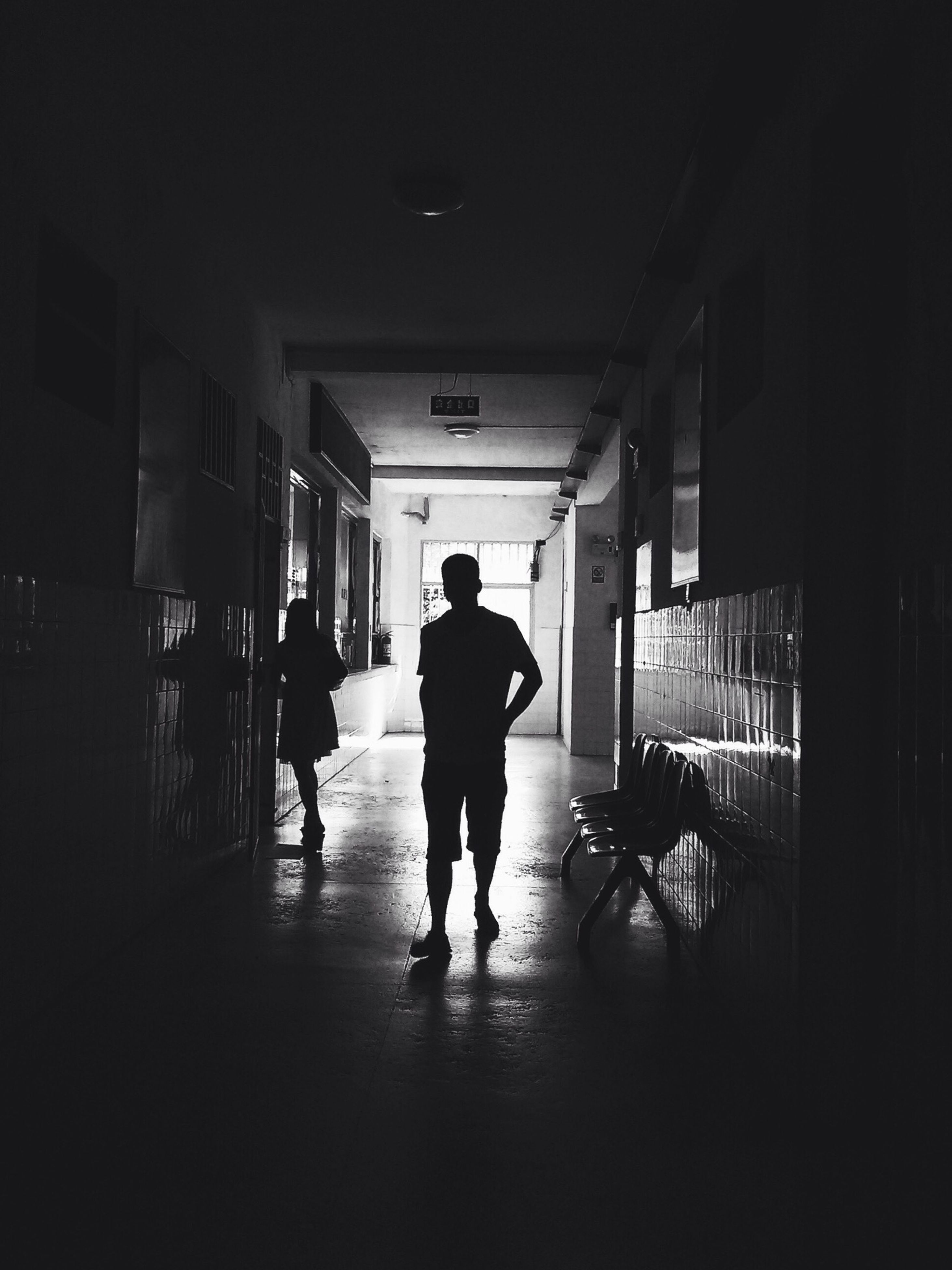 walking, architecture, full length, built structure, men, indoors, rear view, building exterior, lifestyles, city life, city, person, transportation, building, street, on the move, silhouette, illuminated