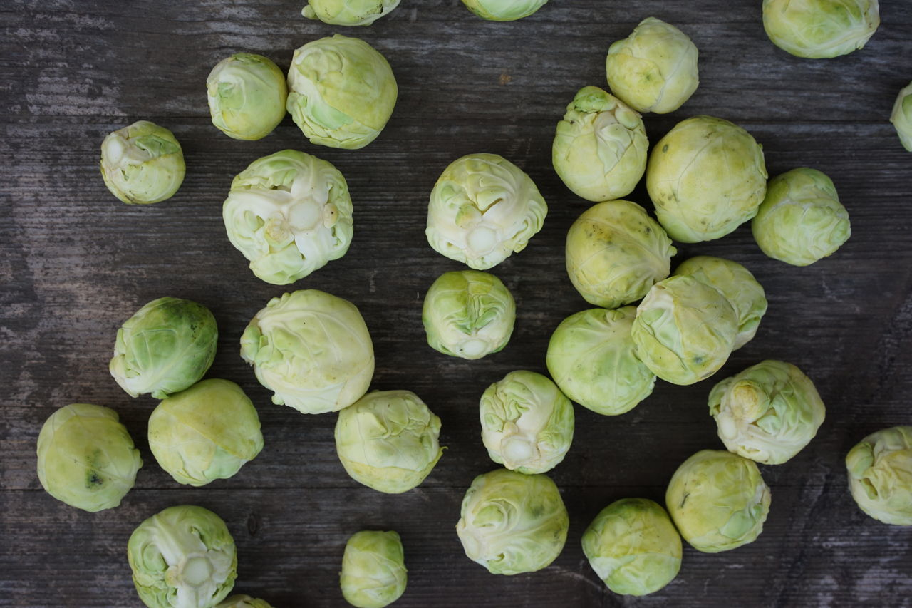 food and drink, vegetable, freshness, healthy eating, high angle view, food, indoors, no people, wood - material, directly above, brussels sprout, green color, close-up, large group of objects, fruit, day