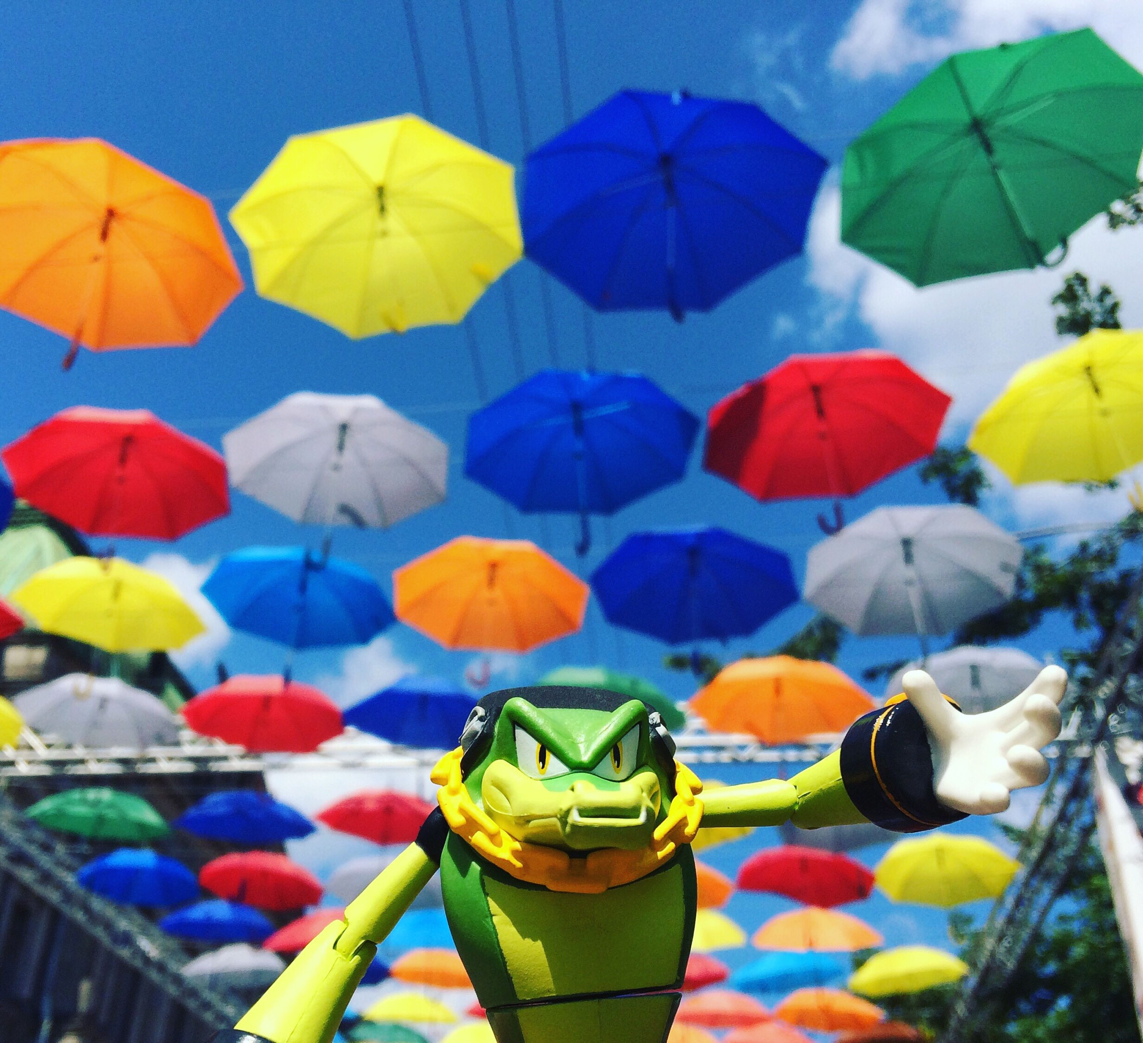 umbrella, multi colored, protection, large group of objects, colorful, tourism, tourist, variation, group of objects, person, holding, outdoors, abundance, arrangement, day, vibrant color, sky, vacations, adventure, red