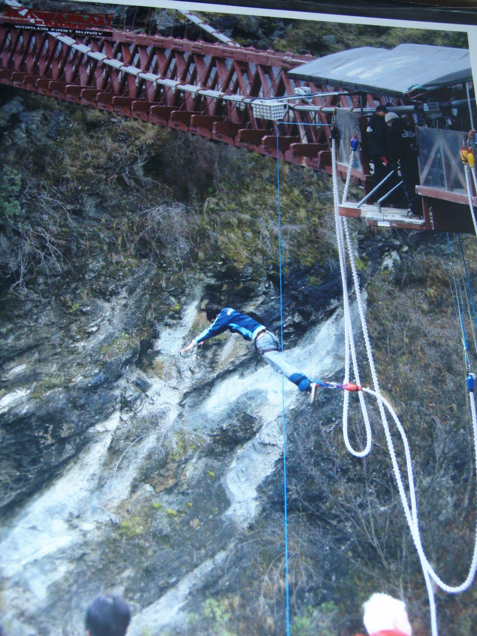 High Angle View Of Man Bungee Jumping Over Rock Formation In Sea