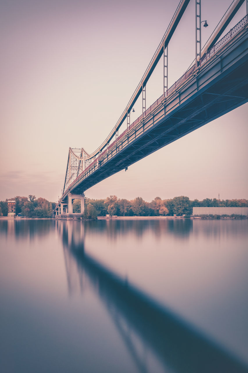 bridge - man made structure, connection, engineering, architecture, transportation, built structure, water, river, waterfront, reflection, travel destinations, suspension bridge, no people, travel, sky, outdoors, clear sky, illuminated, building exterior, city, day, nature