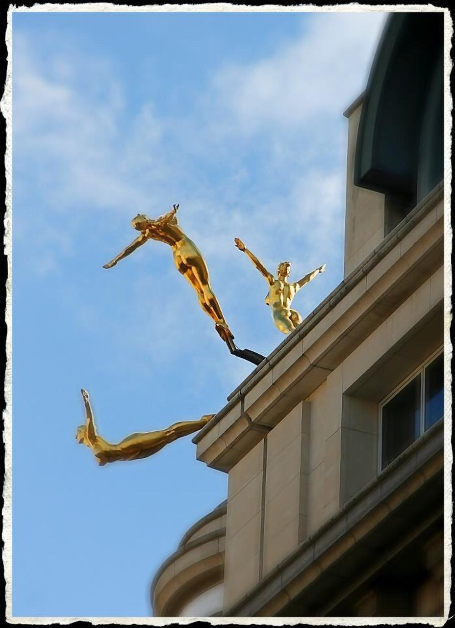 statue, sculpture, architecture, built structure, building exterior, low angle view, human representation, sky, cloud - sky, day, outdoors, no people, architectural column, gold colored, travel destinations, city