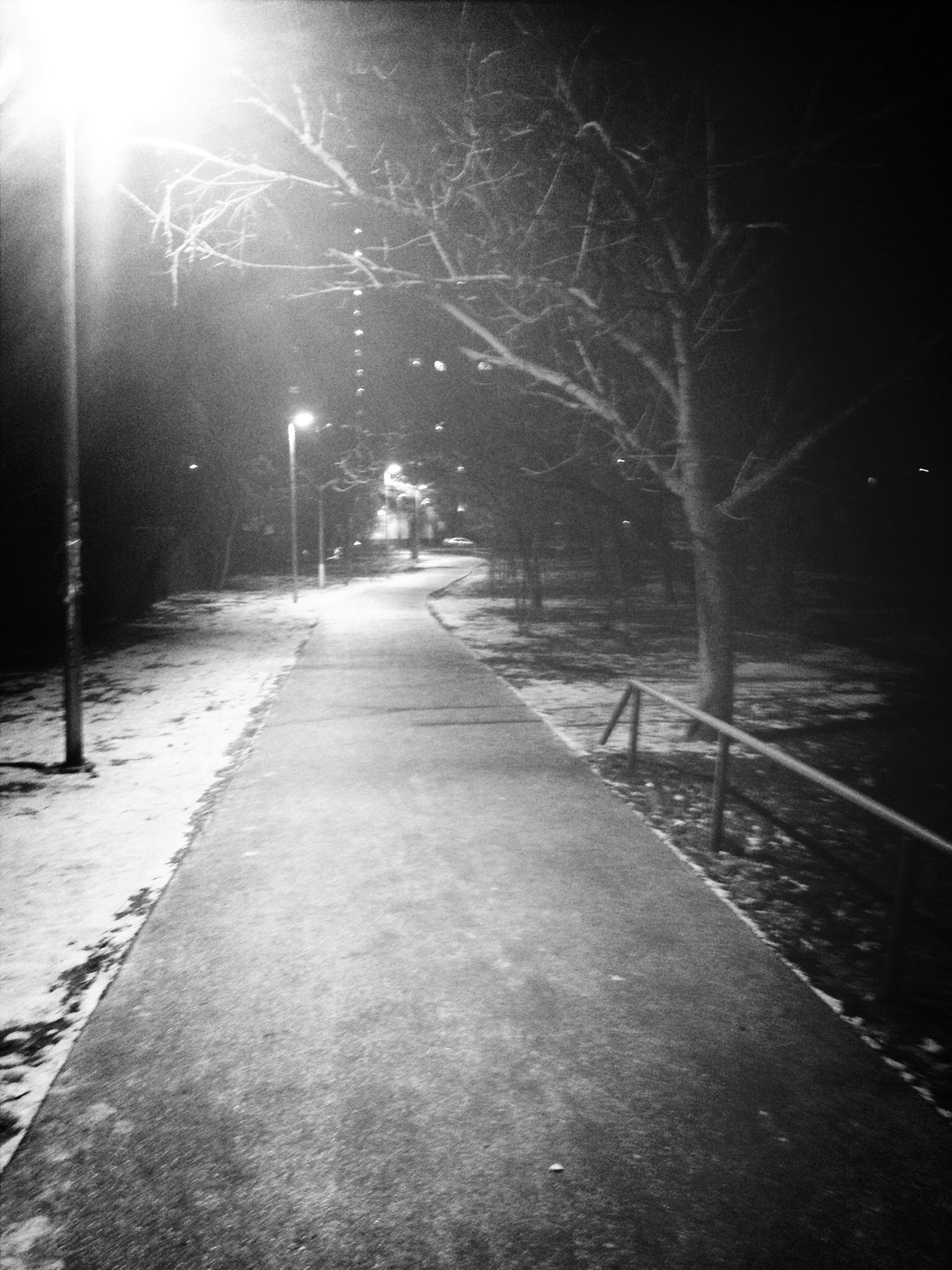 the way forward, illuminated, night, diminishing perspective, street light, vanishing point, lighting equipment, transportation, street, one person, road, railing, sidewalk, lens flare, footpath, outdoors, walkway, tree, season, long