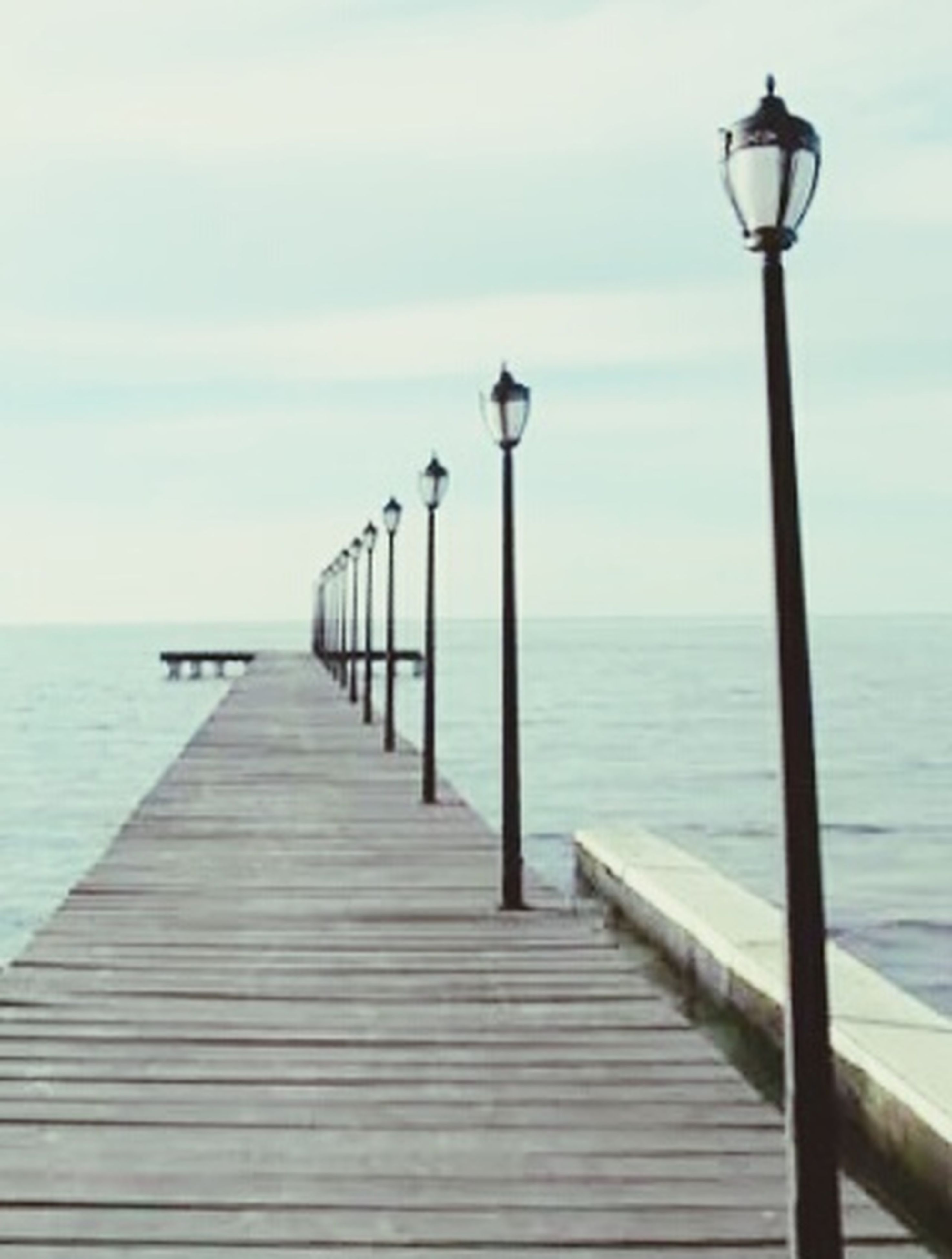 sea, horizon over water, water, pier, the way forward, tranquil scene, tranquility, sky, scenics, railing, street light, beauty in nature, nature, diminishing perspective, idyllic, jetty, wood - material, lighting equipment, long, ocean