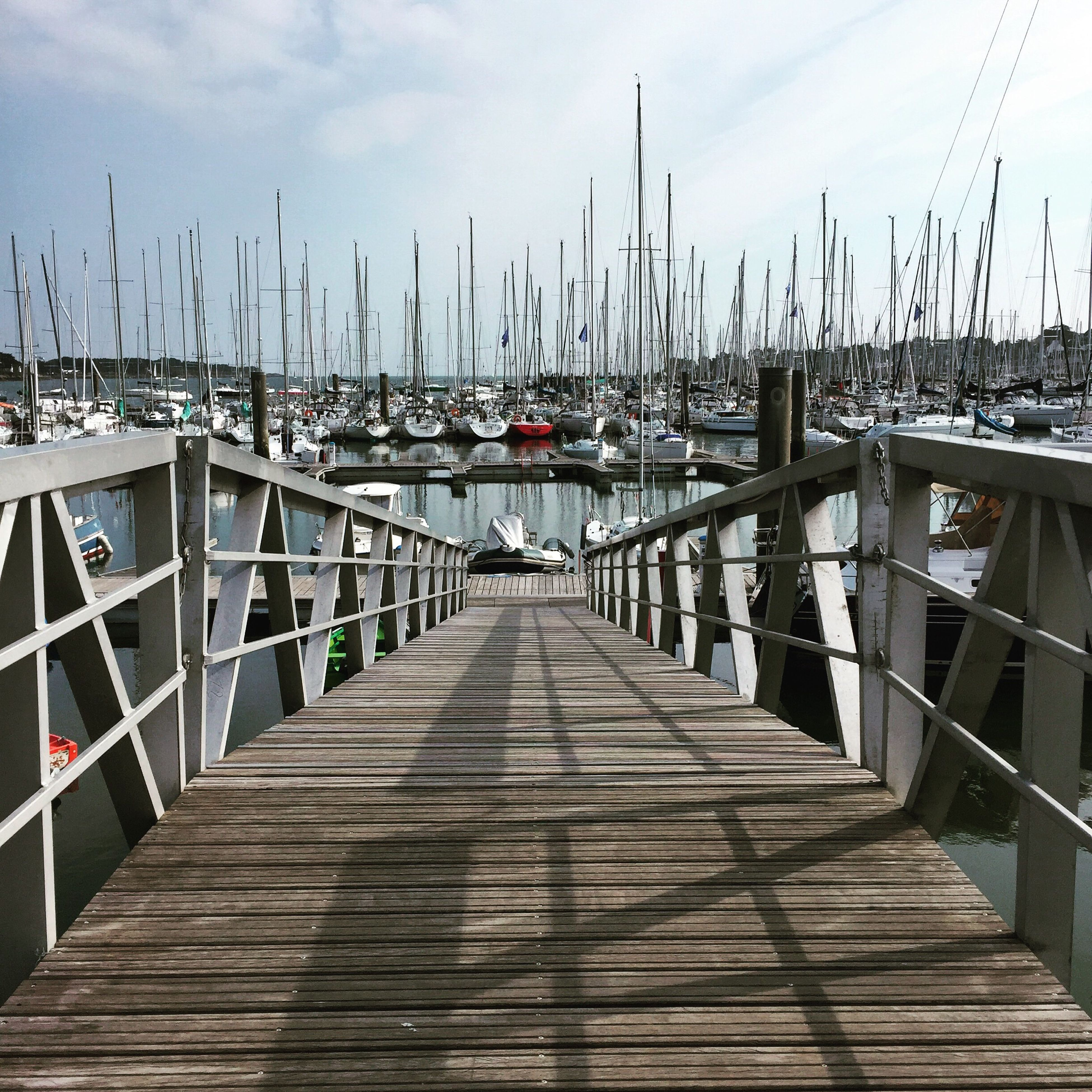 sky, railing, the way forward, pier, water, diminishing perspective, built structure, nautical vessel, transportation, wood - material, sea, architecture, moored, boardwalk, vanishing point, day, harbor, cloud - sky, jetty, boat