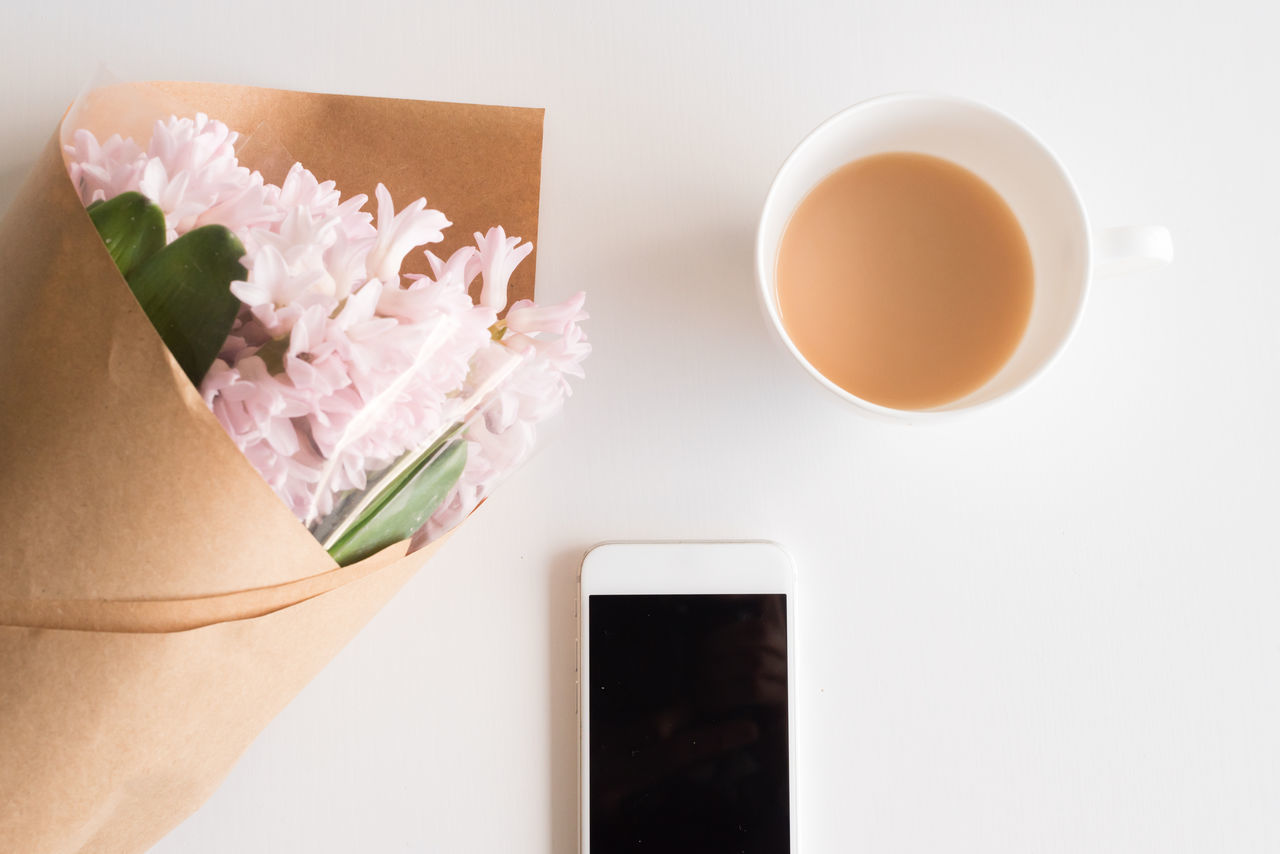 Pink hyacinth flowers, smart phone and cup of tea on white table from above Close-up Coffee Cup Day Drink Flatlay Flower Food And Drink Freshness High Angle View Indoors  No People Refreshment Smart Phone Studio Shot White Background