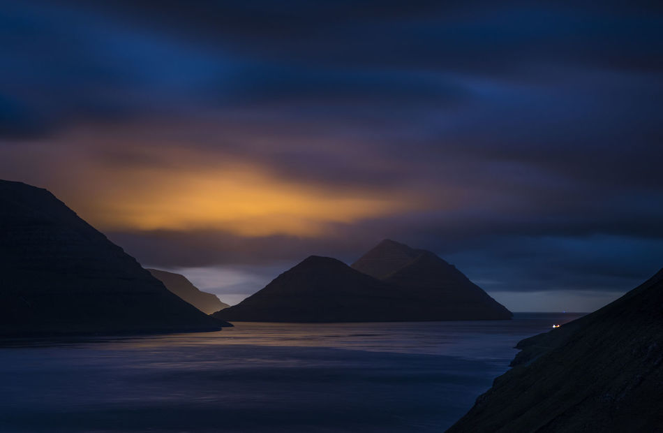 The lights from the city of klaksvik lights up the low clouds just as the blue colors of dusk is about to set in Atmospheric Mood Beauty In Nature Dramatic Sky Dusk Faroe Faroeislands Färöer Mountain Mountain Peak Mountain Range Nature Outdoors Romantic Sky Scenics Sea Silhouette Sky Tranquil Scene Tranquility Vacations Vibrant Color Water