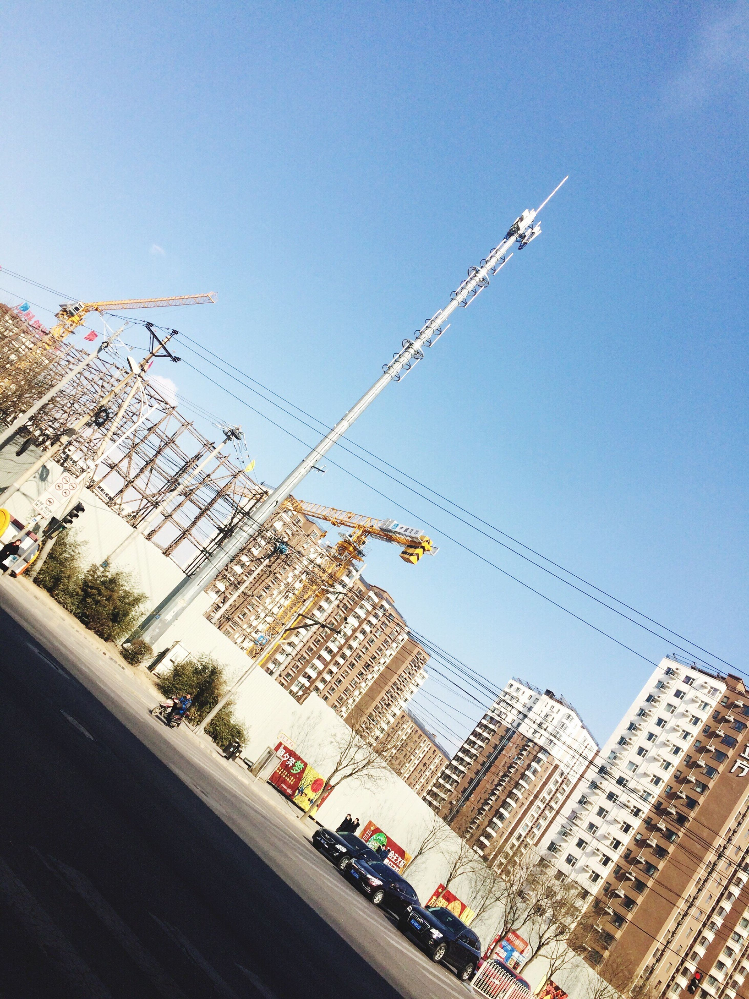 building exterior, architecture, built structure, low angle view, city, clear sky, sky, tall - high, building, city life, skyscraper, crane - construction machinery, day, development, tower, outdoors, tilt, modern, construction site, office building