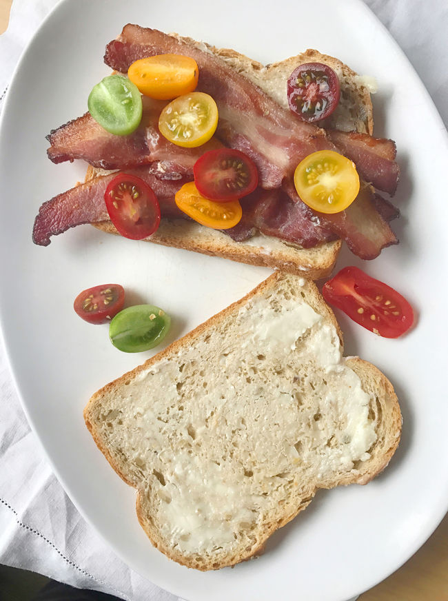Bacon sandwich from overhead Bacon Butty Bacon Sandwich Bread Cherry Tomatoes Close-up Day Fabric Fatty Meat Indoors  Lunch Meal Napkin No People Overhead Phone Camera Platter Pork Savory Food Snack Tasty Textures