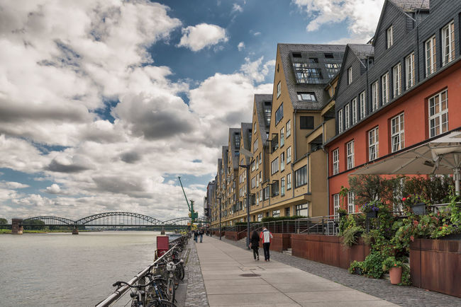 COLOGNE, GERMANY - SEPTEMBER 10, 2017: Unidentified individuals walk from Rheinau-harbor towards the Southern Bridge and enjoy the scenic view on river Rhine Architecture Cologne, Rhine, Rheinau-Harbor High Resolution Modern Sightseeing Blue Sky Business Finance And Industry City Scape Colorful Historic Leisure Time Magnificant Rheinauhafen Travel Destination# Urban Living