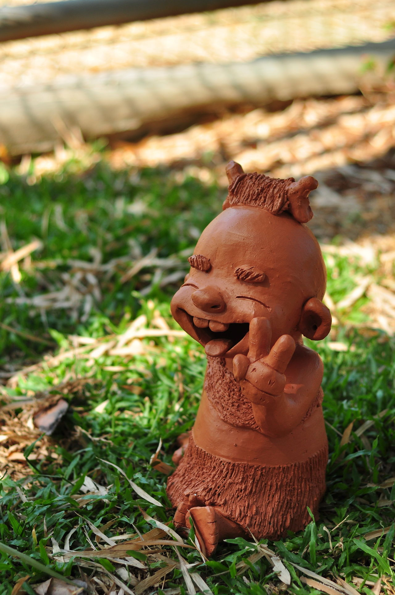 The tribal children's clay smiles cheerfully. Allright Barbarian Child Close-up Cute Day Earthenware Field Fingers Glad Grass Have Fun Human Representation Jovial Kid Laugh No People Outdoors Sculpture Smile Statue Sunlight Teeth Tribe