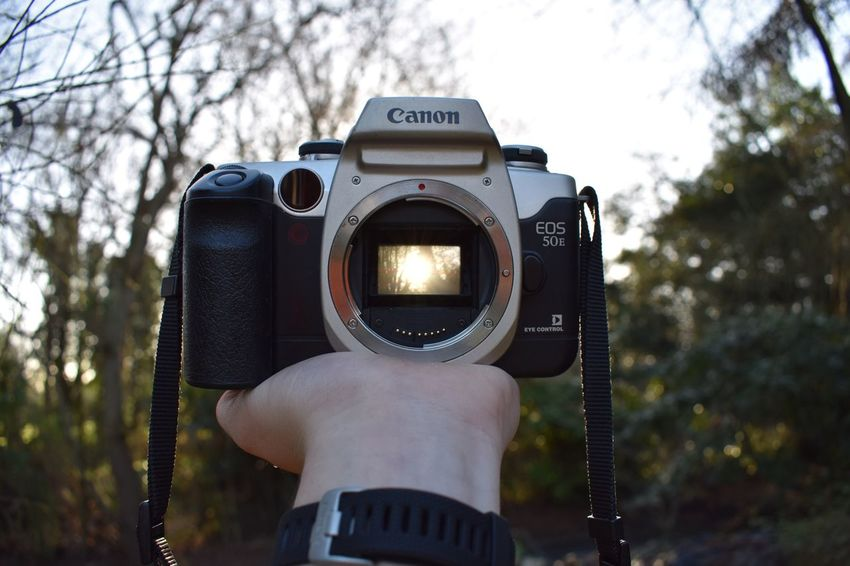 Photography Themes Camera - Photographic Equipment Tree Photographing Human Body Part Focus On Foreground Digital Camera Holding Photographic Equipment Technology Close-up Television Camera Sky SLR Camera One Person Outdoors Lens - Eye Home Video Camera Digital Single-lens Reflex Camera