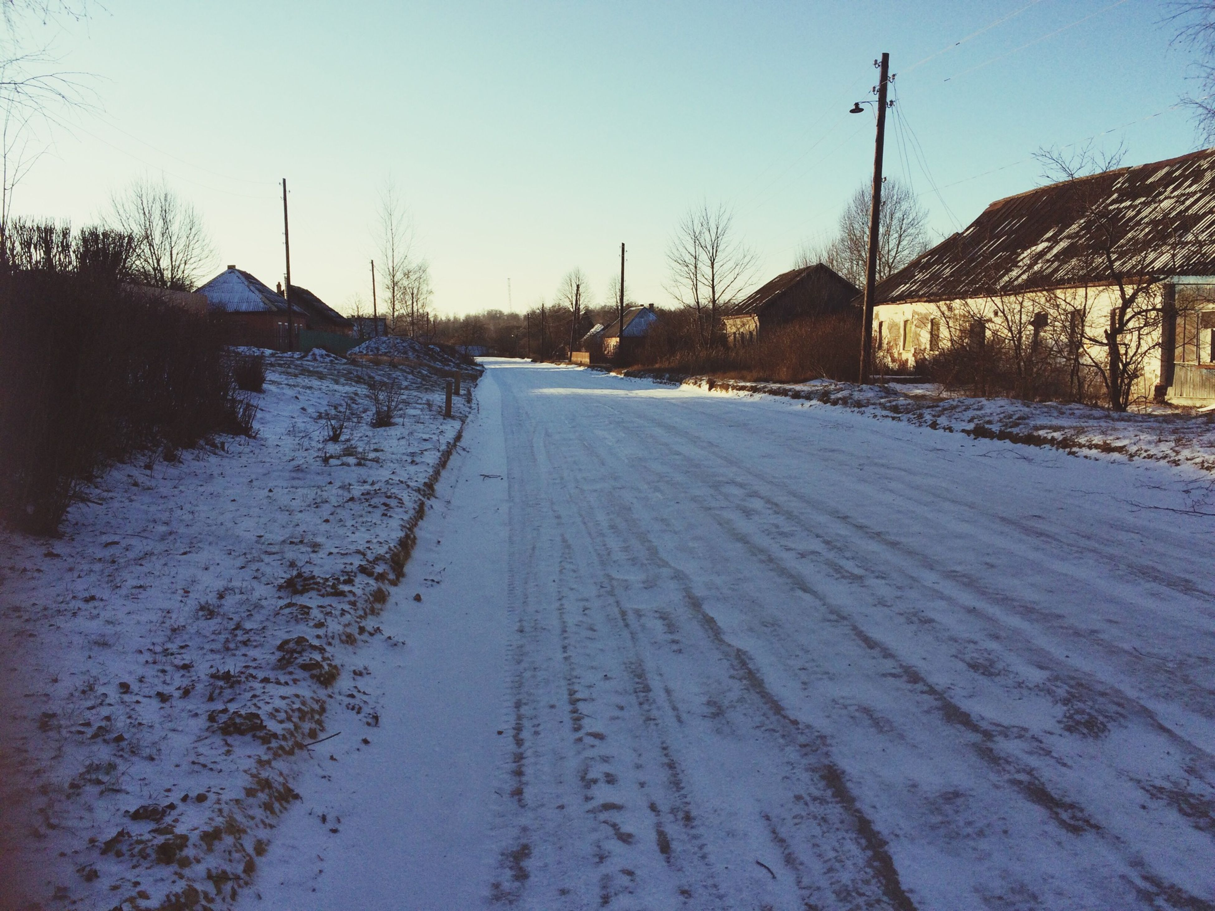 snow, winter, cold temperature, the way forward, season, building exterior, clear sky, built structure, architecture, electricity pylon, transportation, power line, diminishing perspective, house, street, sky, road, weather, vanishing point, frozen