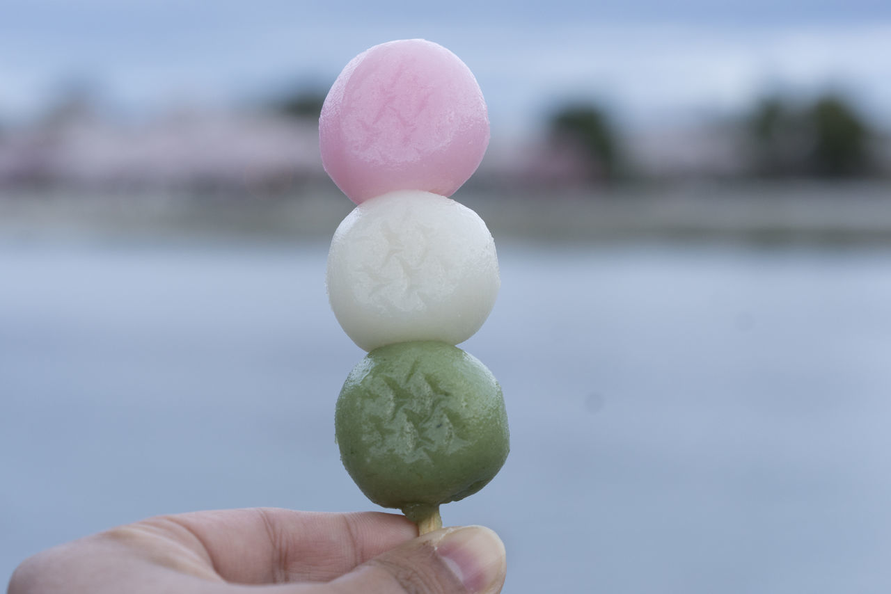 Close-Up Of Cropped Hand Holding Dango