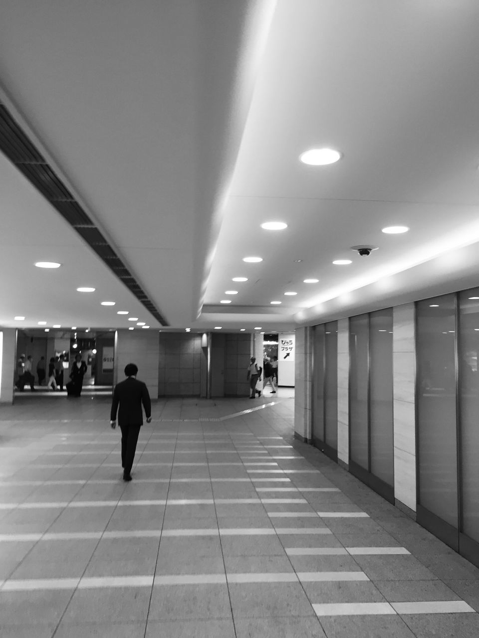 illuminated, ceiling, lighting equipment, indoors, walking, real people, men, modern, architecture, one person, people