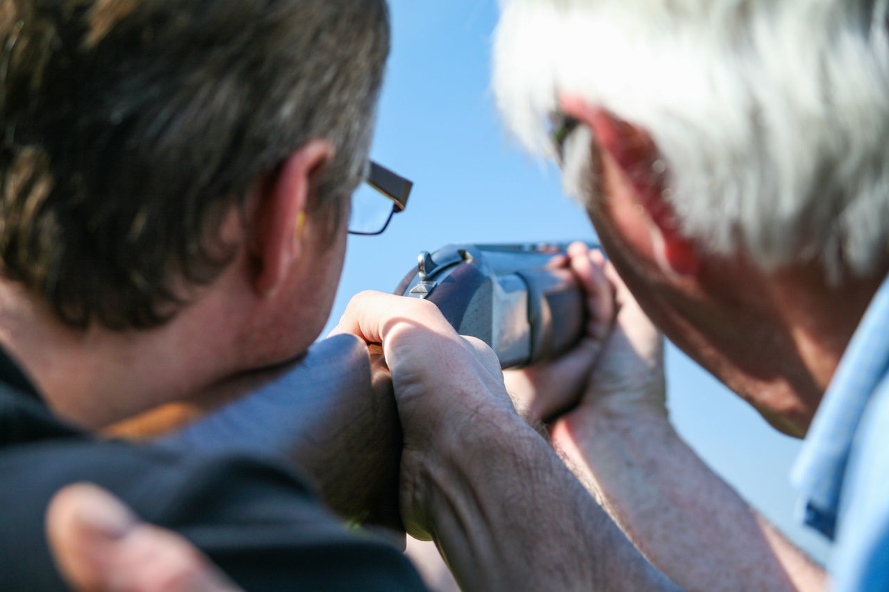 One man teaches another how to aim a rifle at a clay pigeon shooting range Teach Coach Aim Rifle Clay Pigeon Shoot Novice Expert Stag Party Event Looking Down The Barrel Of A Gun Hunt Practice Gun Ready Target Steady Sport Game Outdoor