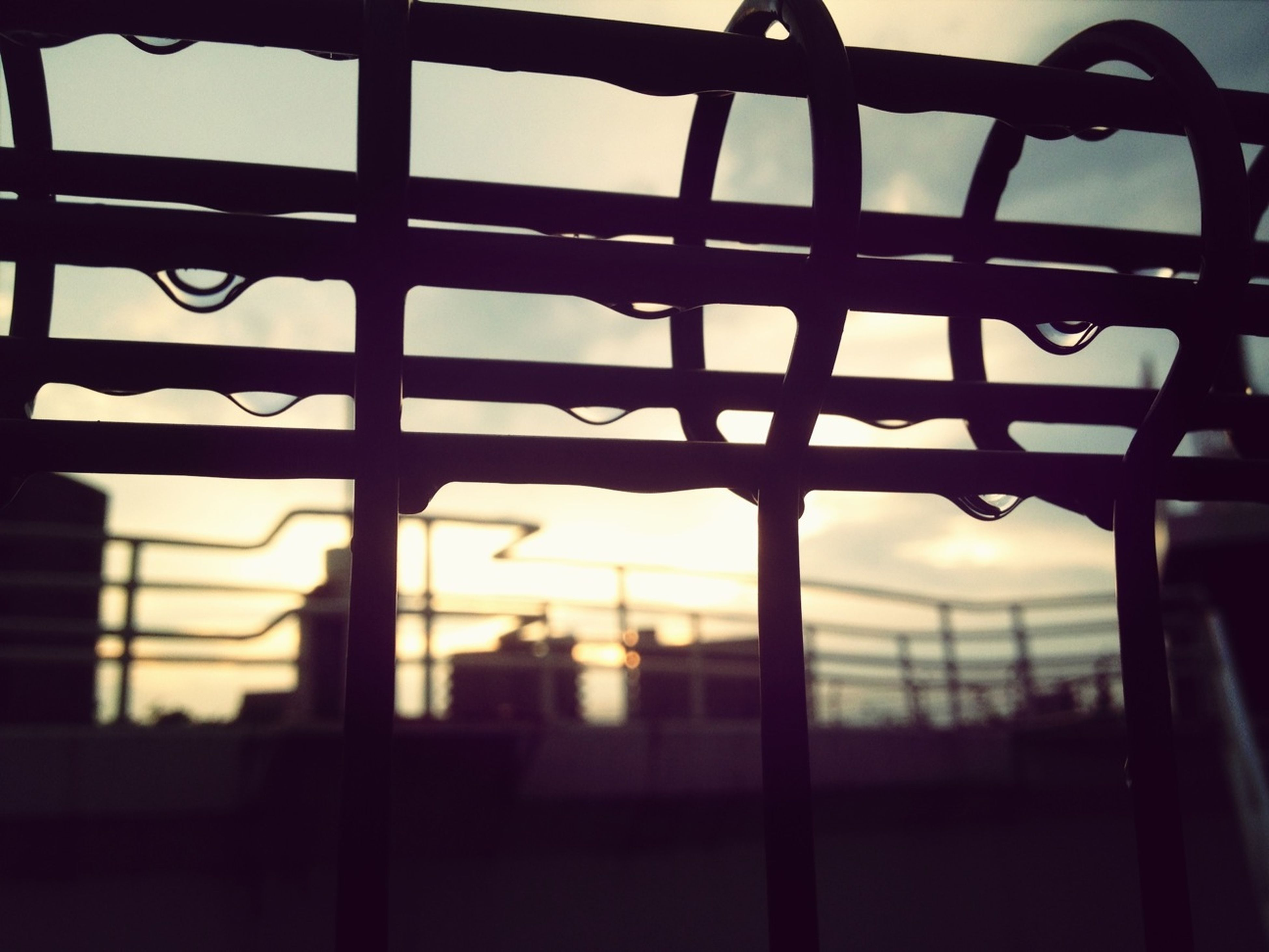 silhouette, focus on foreground, sunset, window, indoors, sky, built structure, metal, architecture, close-up, protection, fence, safety, glass - material, building exterior, pattern, focus on background, no people, security, selective focus