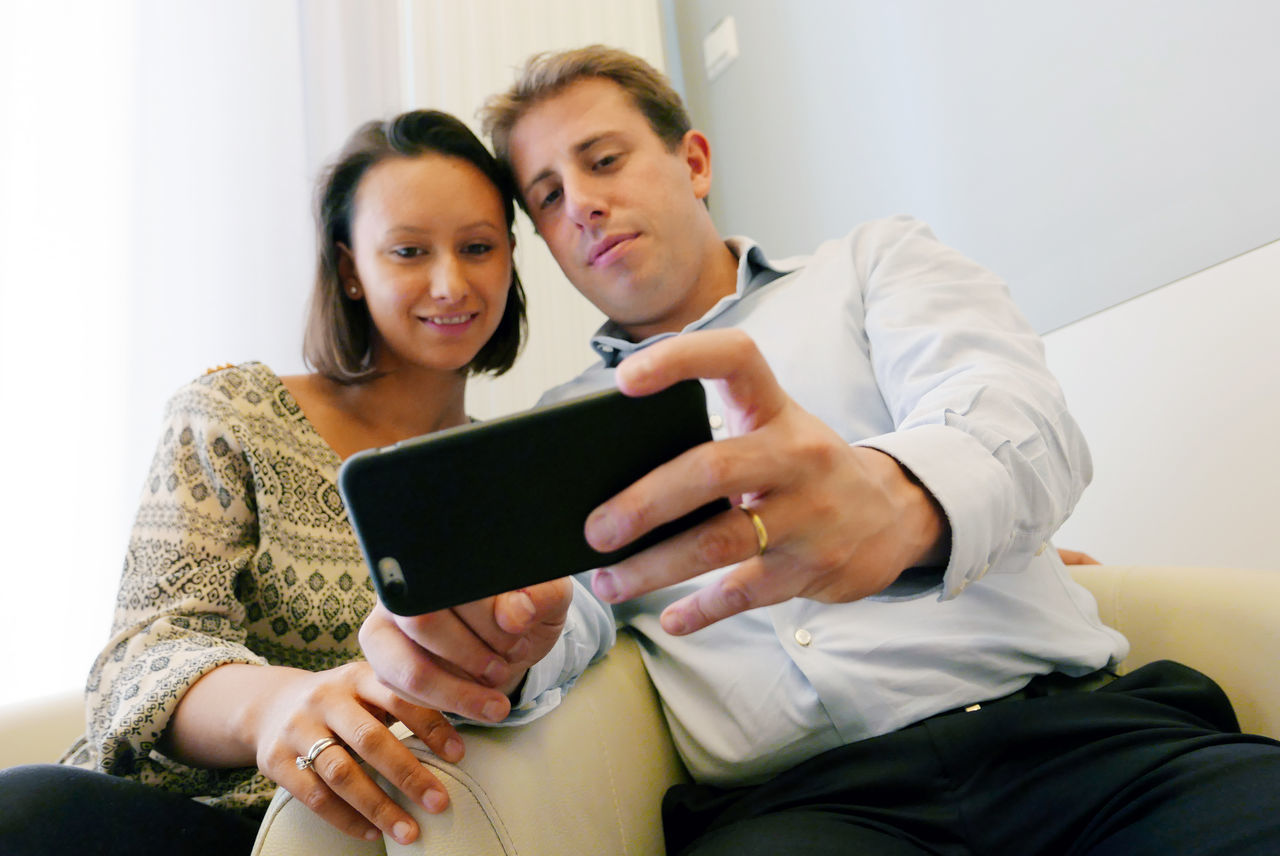two people, real people, indoors, young adult, wireless technology, sitting, young women, togetherness, leisure activity, technology, connection, lifestyles, front view, casual clothing, communication, home interior, holding, bonding, day