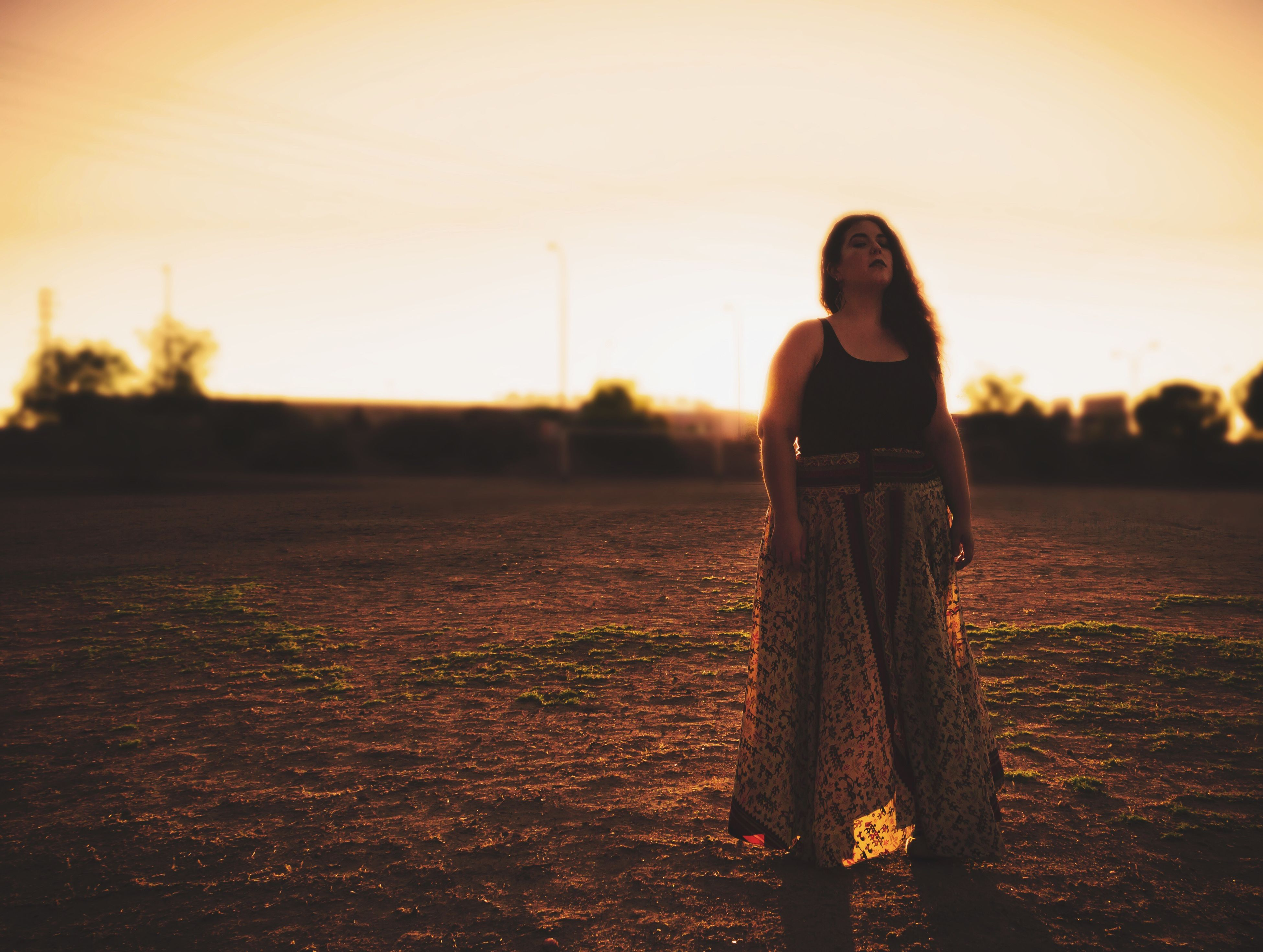 sunset, one person, standing, full length, front view, real people, young adult, young women, lifestyles, outdoors, beautiful woman, focus on foreground, sky, portrait, leisure activity, looking at camera, nature, one young woman only, tree, day, adult, people