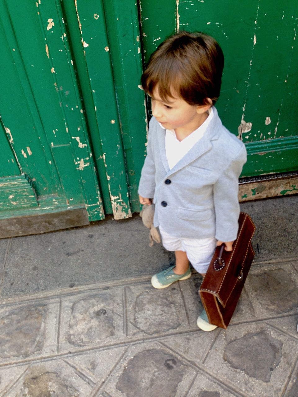 High Angle View Of Cute Boy With Briefcase Against Green Wooden Door