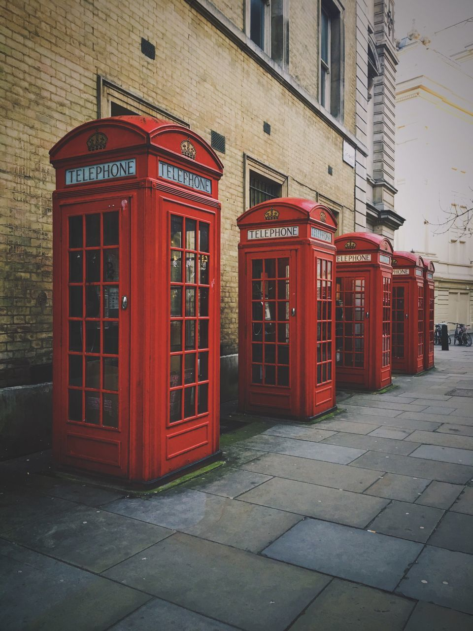 communication, telephone booth, red, building exterior, built structure, pay phone, architecture, connection, outdoors, convenience, day, telephone, no people, street, telecommunications equipment, technology, city