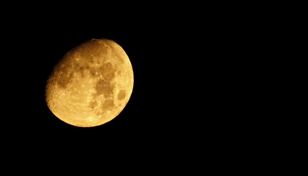 moon, night, astronomy, moon surface, beauty in nature, nature, planetary moon, copy space, scenics, low angle view, tranquility, outdoors, no people, yellow, clear sky, space exploration, space, sky, close-up