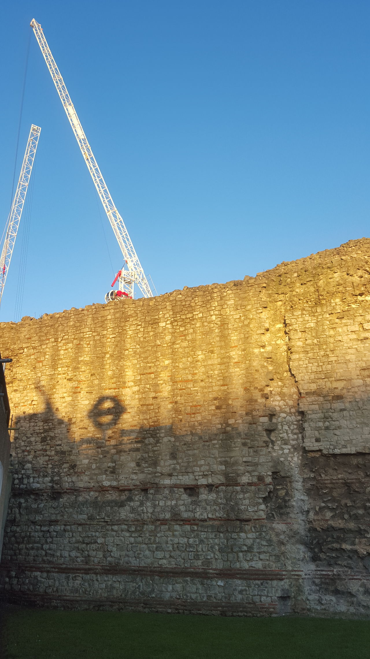 (Very) old London in front of future to be London. At Towerhill Londonwall Sunset_collection Cranes building the next gen of London's Buildings tower over the Roman and medieval wall. The shadow is the london undeground sign roundel.
