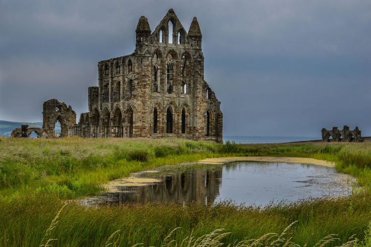 Whitby Abbey, Yorkshire, England, UK Abbey Ancient Ancient Civilization Architecture Building Exterior Built Structure Cloud - Sky Day Grass History Monastic Nature No People Old Ruin Outdoors Place Of Worship Pool Reeds Sky Spirituality Travel Destinations Water Whitby Whitby Abbey Yorkshire
