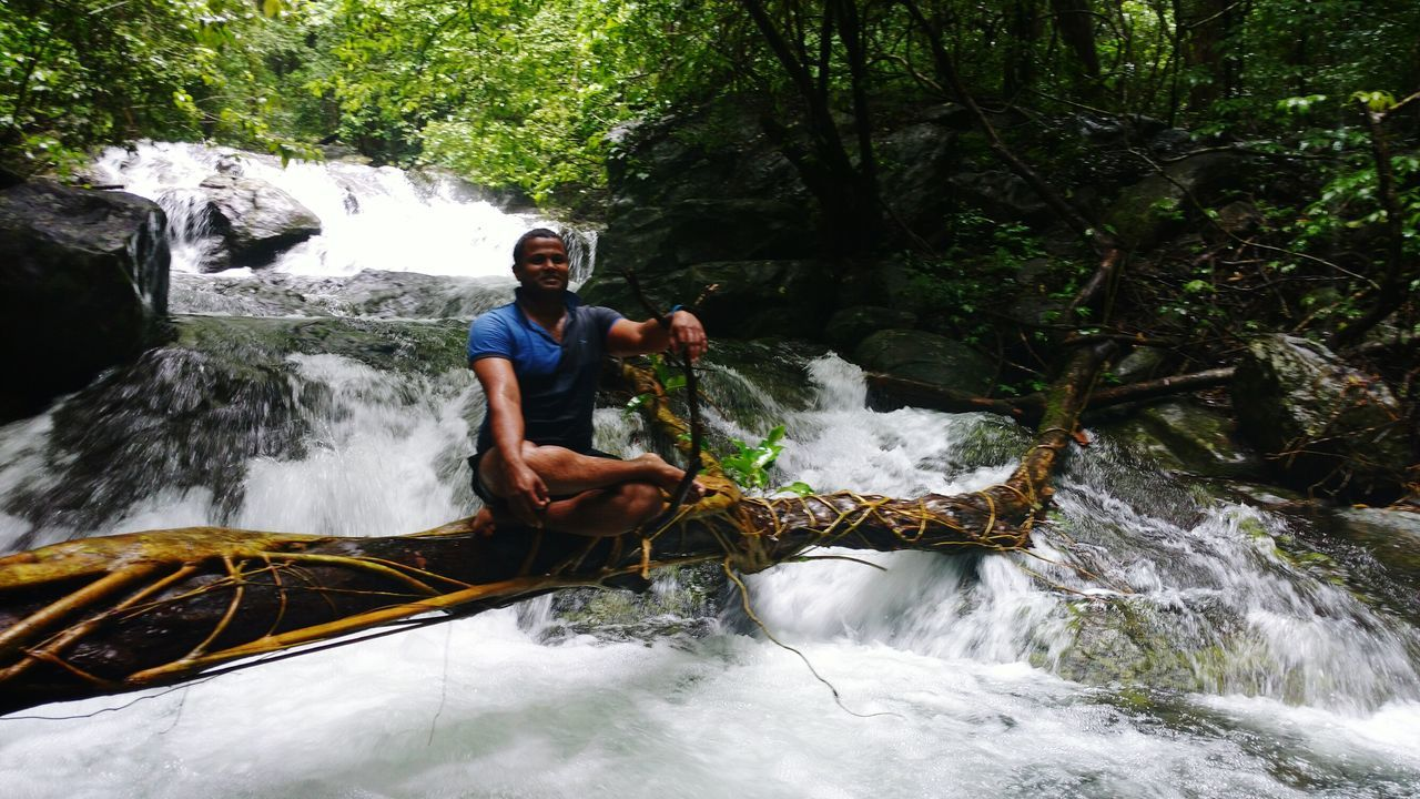 waterfall, rock - object, adventure, river, nature, real people, water, beauty in nature, outdoors, one person, rafting, day, motion, oar, raft, tree, extreme sports, young adult, people