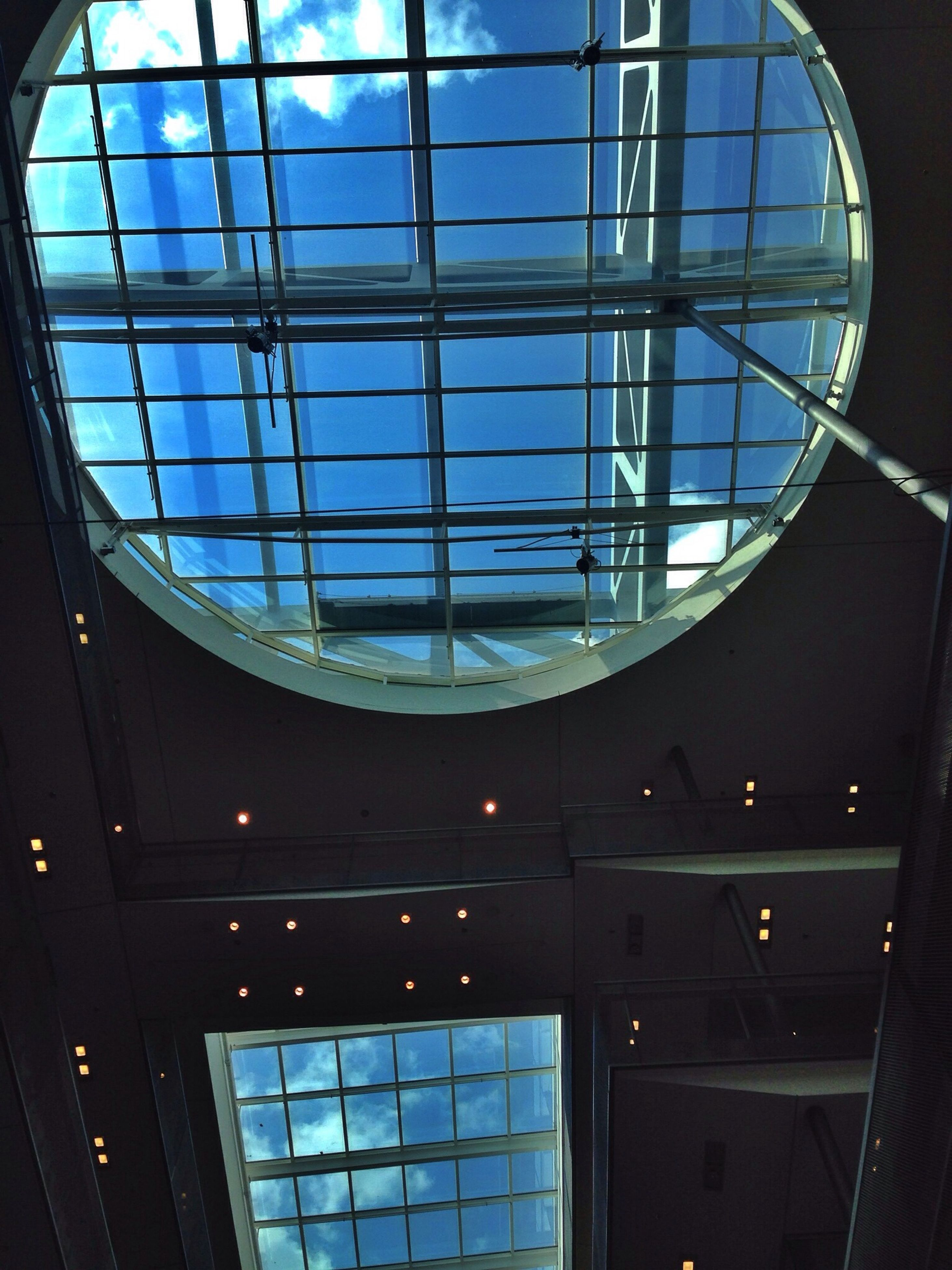 architecture, indoors, glass - material, built structure, window, transparent, modern, low angle view, reflection, skylight, building exterior, building, ceiling, interior, glass, architectural feature, geometric shape, sky, no people, day