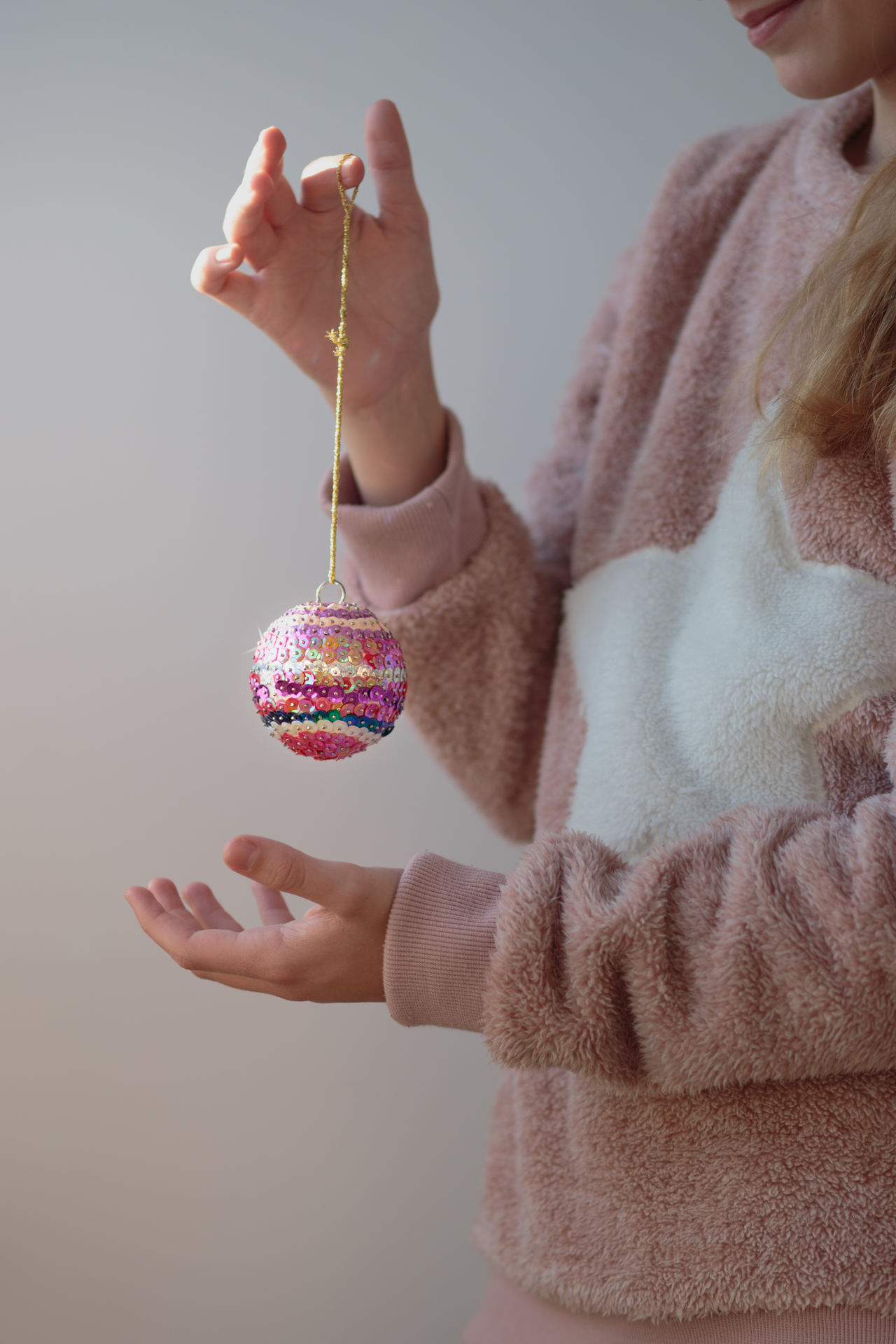 Young girl enjoying her handmade colorful Christmas ball Anonymous Ball Christmas Christmastime Close-up Craft Decorating Decoration Female Girl Holding Holiday Homemade One Ornament Person Tradition Traditional