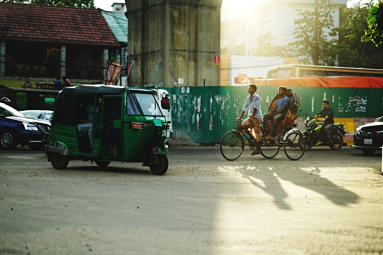 Transportation Built Structure Bicycle Sunlight Mode Of Transport Architecture Building Exterior Street Day Road Land Vehicle Real People City Life Cycling Rickshaw Shadow Streetphotography Chittagong OpenEdit Light And Shadow