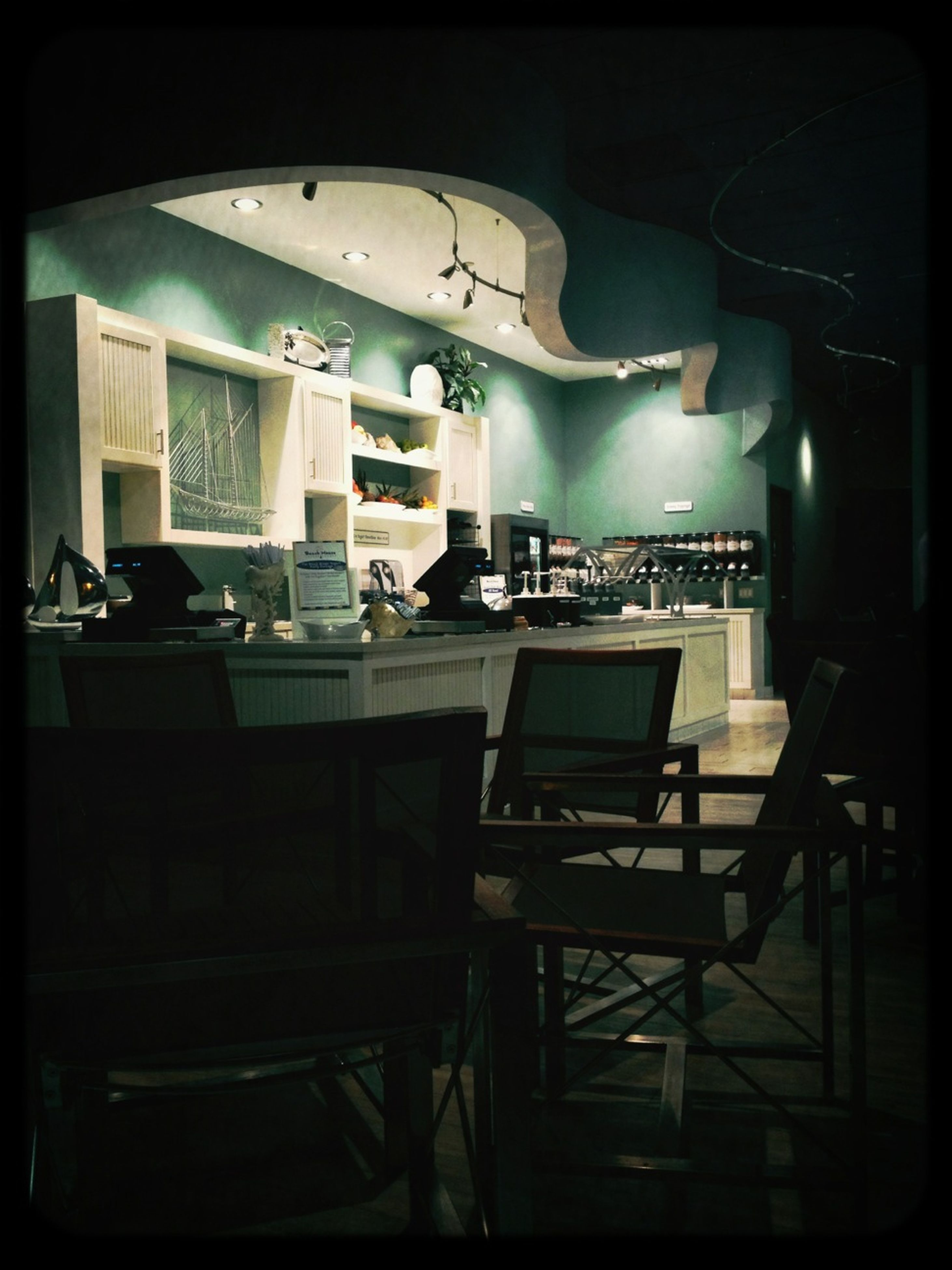 indoors, transfer print, chair, auto post production filter, illuminated, table, absence, empty, restaurant, window, lighting equipment, home interior, interior, seat, room, shelf, no people, glass - material, night, arrangement