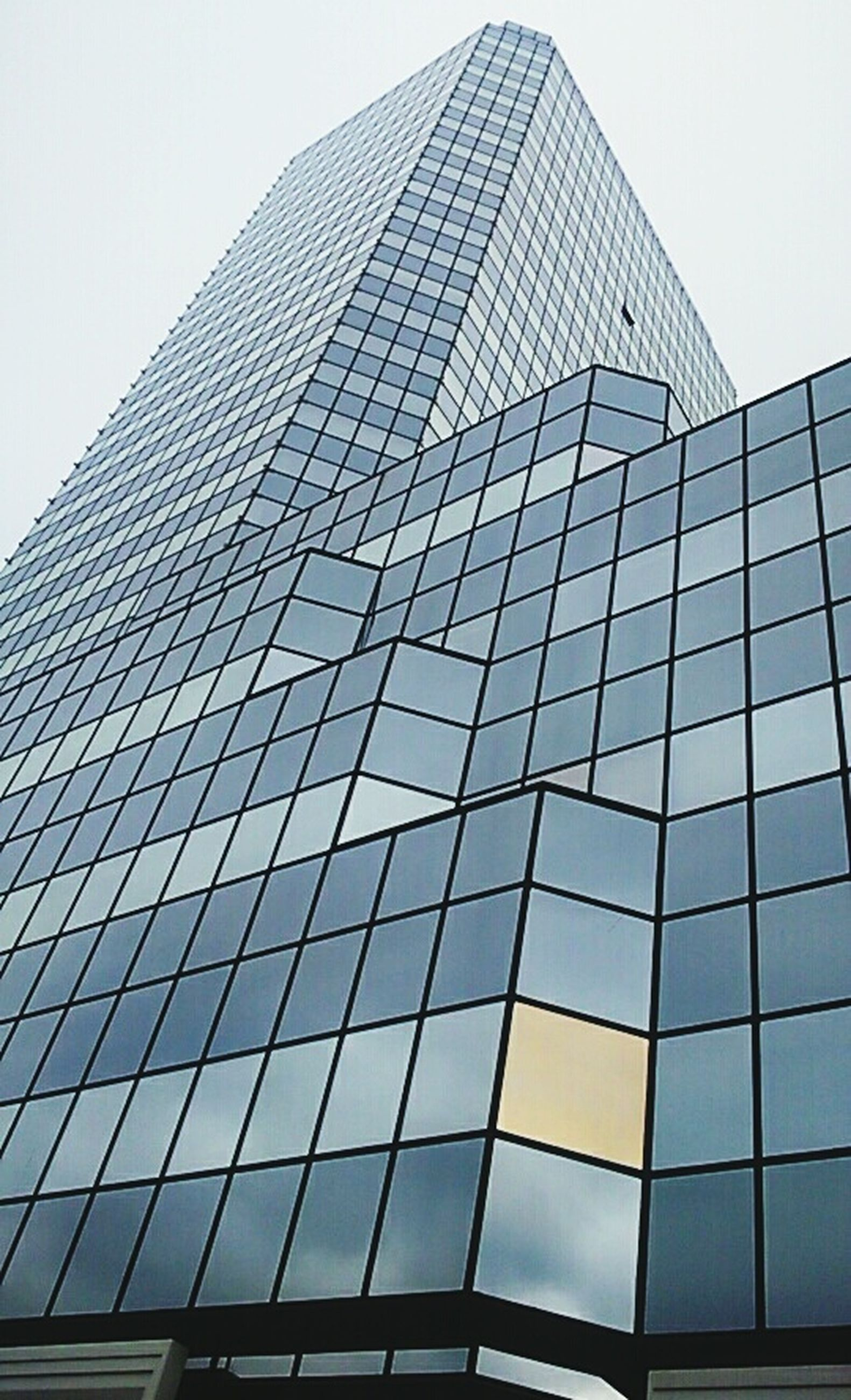 low angle view, building exterior, architecture, built structure, modern, office building, skyscraper, clear sky, tall - high, city, glass - material, building, tower, sky, reflection, day, window, pattern, outdoors, no people