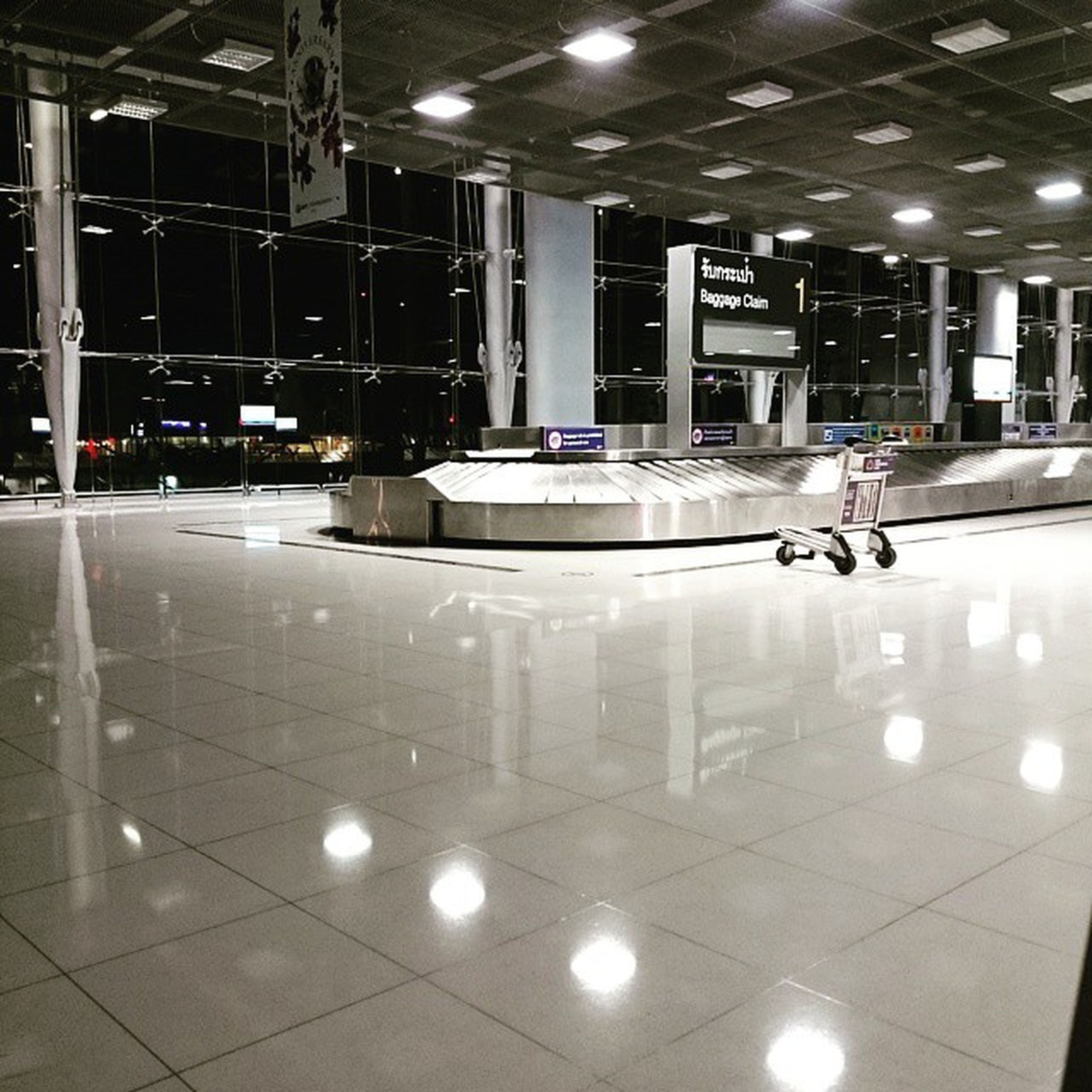 indoors, illuminated, lighting equipment, ceiling, flooring, night, built structure, architecture, reflection, interior, tiled floor, glass - material, light - natural phenomenon, tile, empty, window, transparent, modern, incidental people